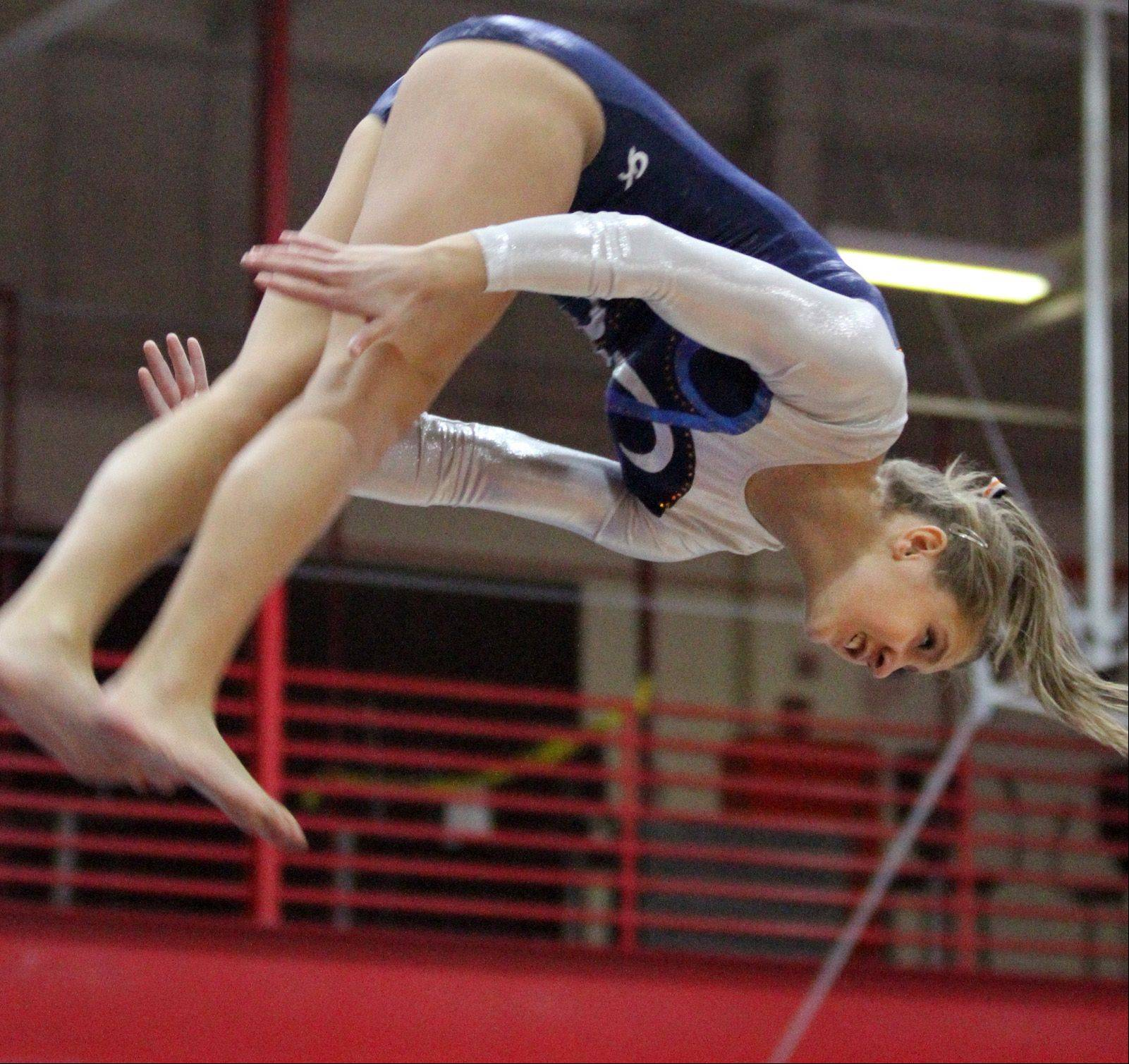 Naperville North's Shelby Porter dismounts from the vault at Palatine invitational girls gymnastics meet in Palatine on Saturday.