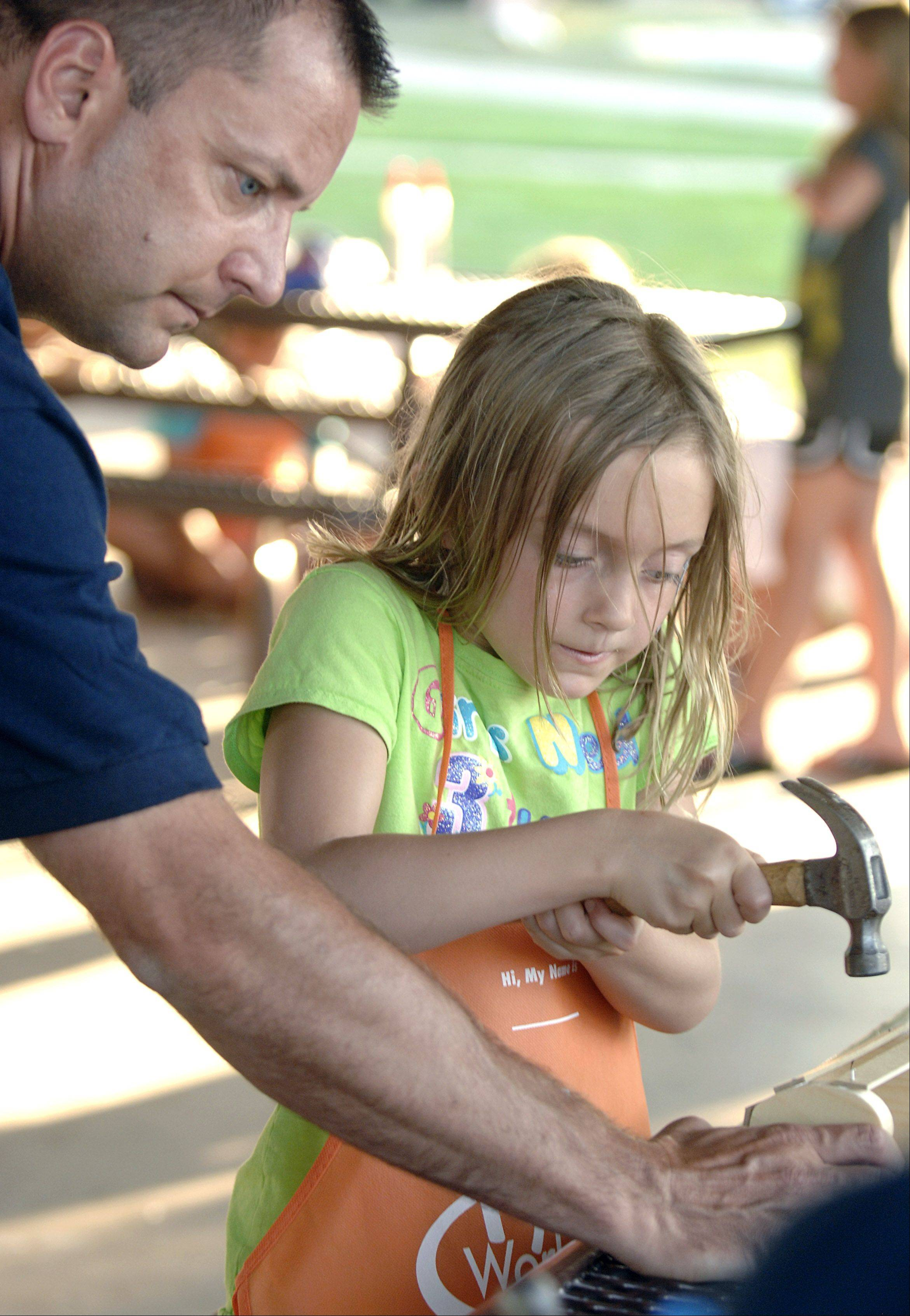 Bartlett Deputy Police Chief Patrick Ullrich helps his daughter, Ava, 7, with a wood craft at the city�s National Night Out pre-party at Jim Jensen Pavilion last August.