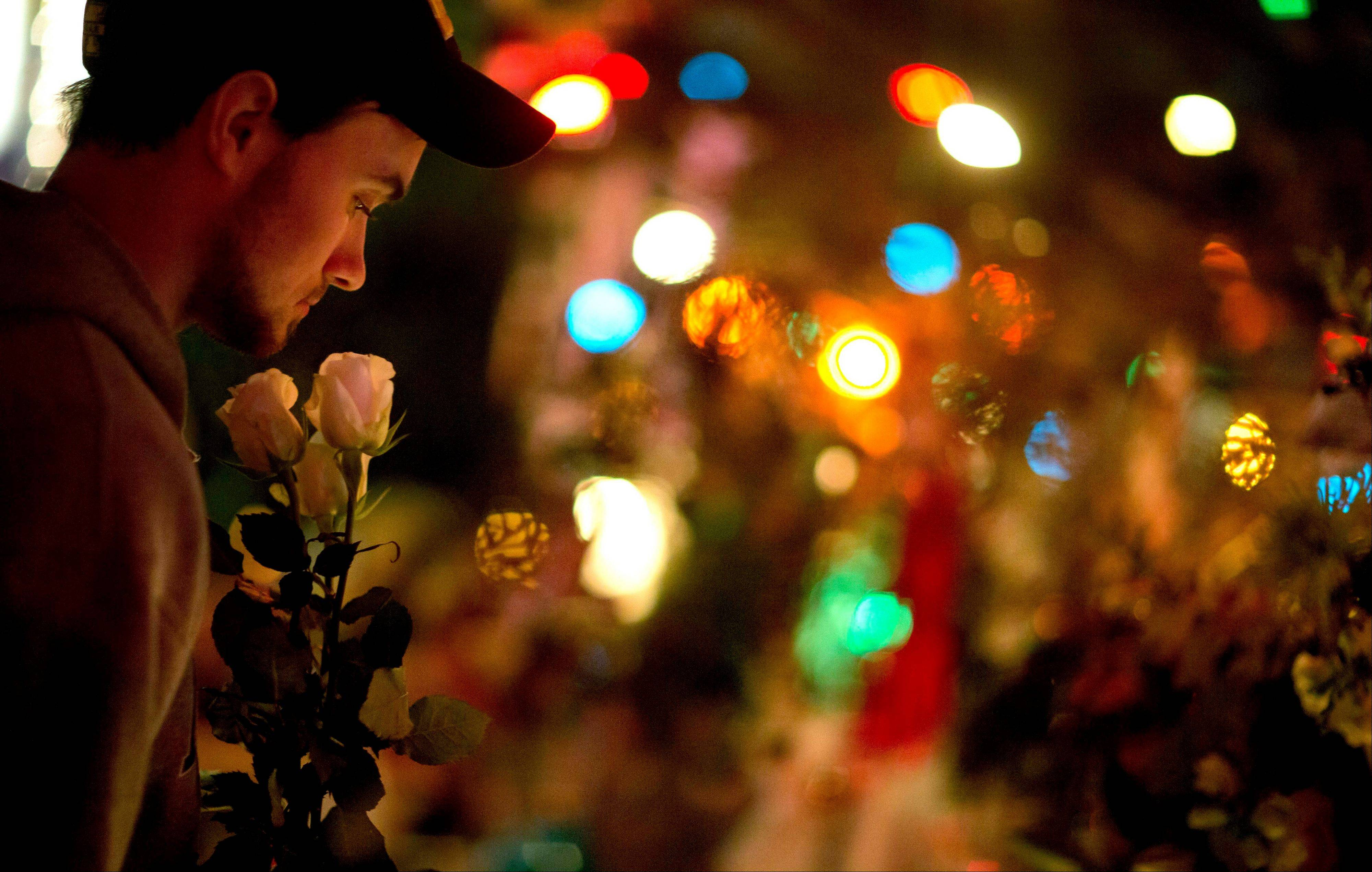 A Newtown resident who identified himself only as Andrew, holds roses as he visits a memorial for the Sandy Hook Elementary School shooting victims, Tuesday in Newtown, Conn.