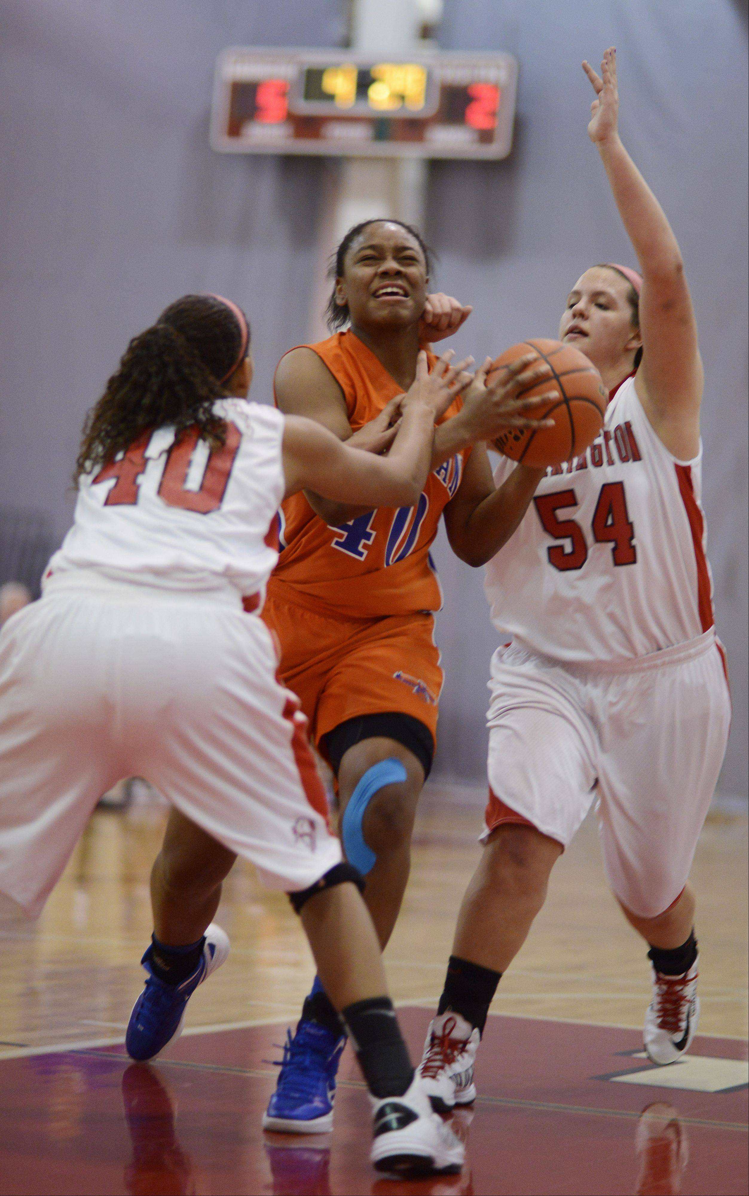 Hoffman Estates� Destinee Young, middle, draws contact as she drives to the basket against Barrington�s Bryana Hopkins, left, and Alexa Resch during Wednesday�s game.