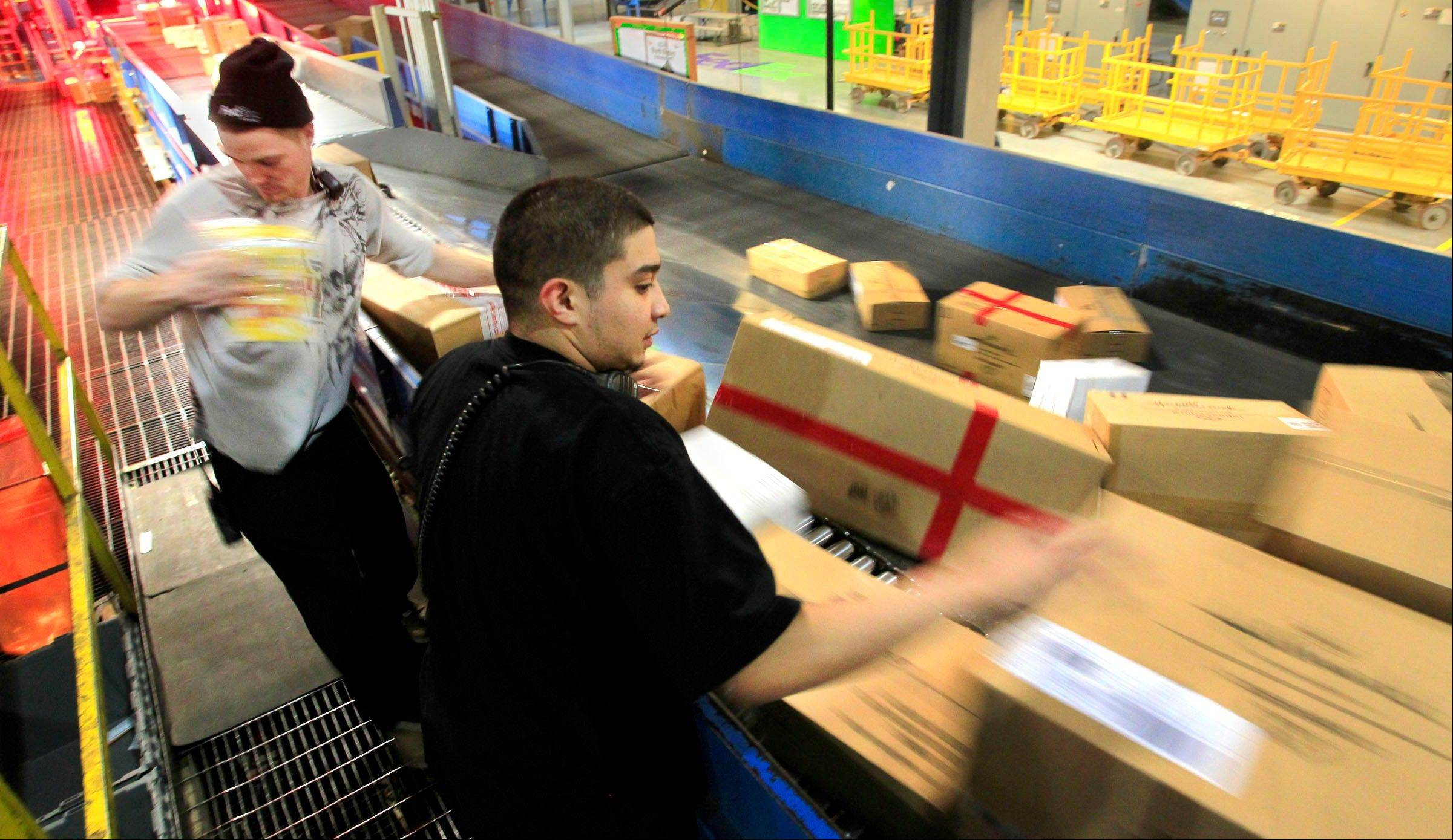 Package handlers J.D. Mansfield, left, and Carlos Campos position incoming packages for bar code scanning going through the Kansas City, Mo., FedEx Ground Hub Tuesday.