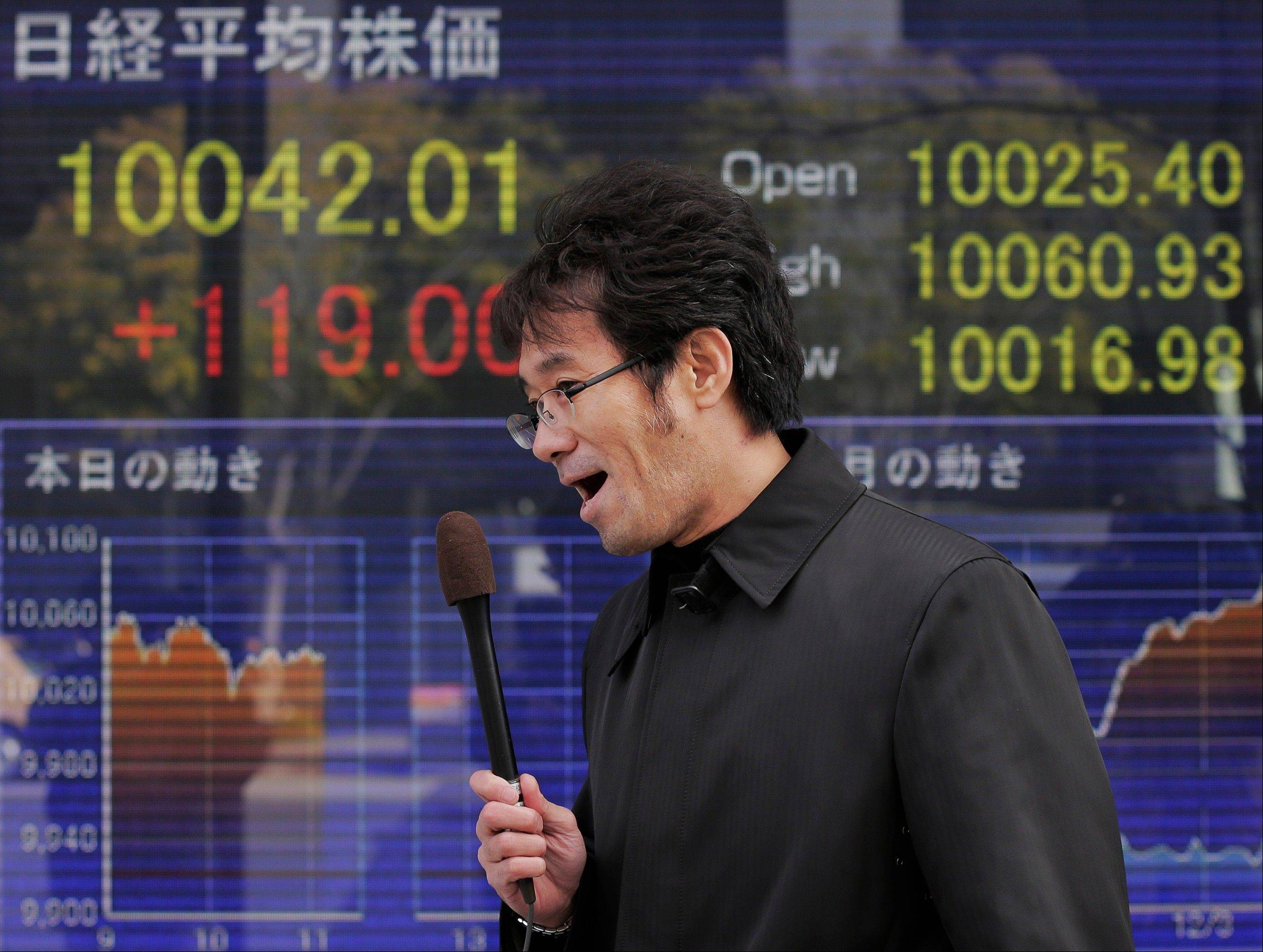A TV journalist reports in front the electronic stock board of a securities firm showing Japan's Nikkei 225 index that rose 119.00 points to 10,042.01 in Tokyo Wednesday morning.