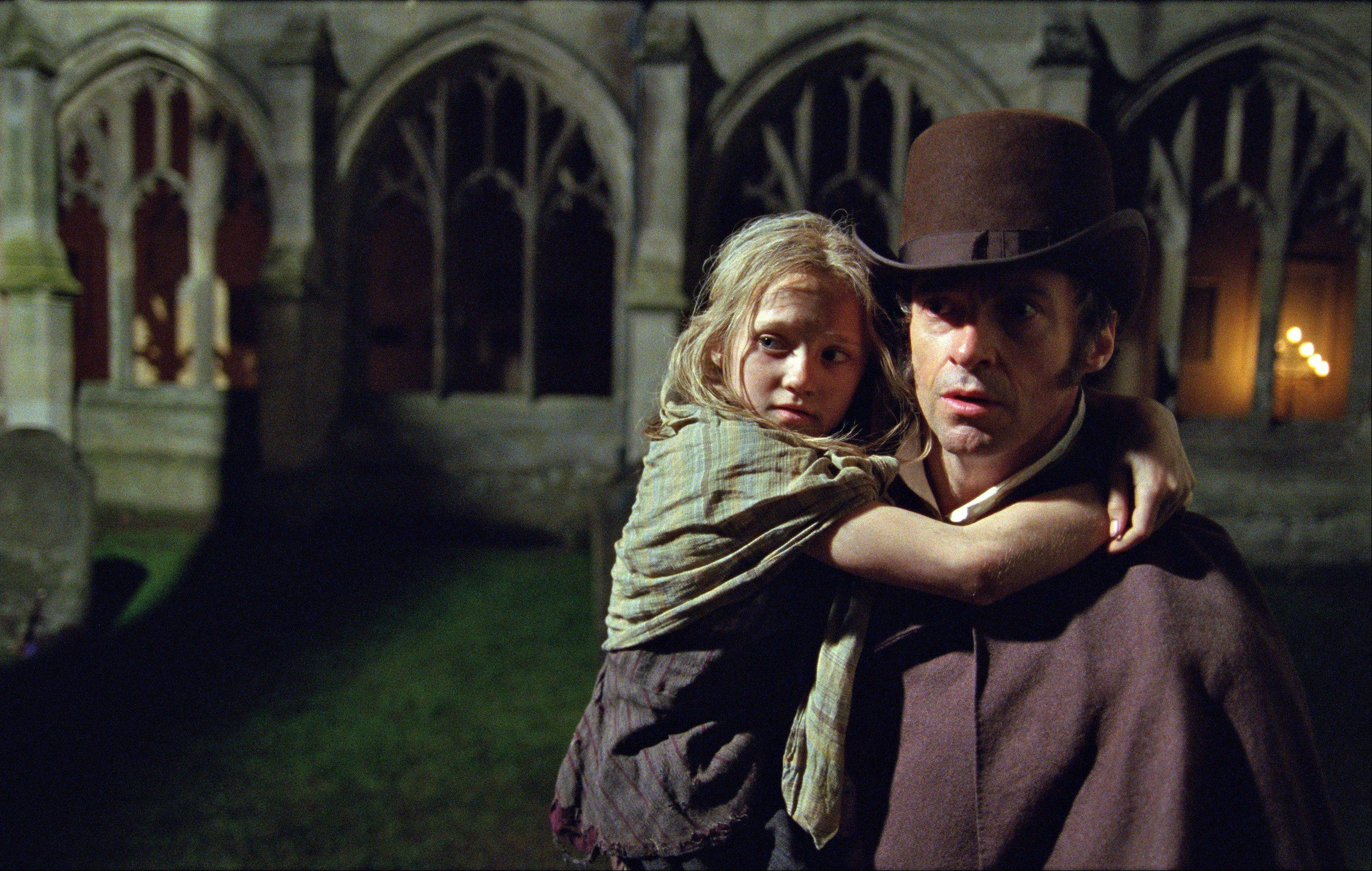 "Fugitive-turned-businessman Jean Valjean (Hugh Jackman) rescues an orphan (Isabelle Allen) in the pop opera ""Les Miserables."""