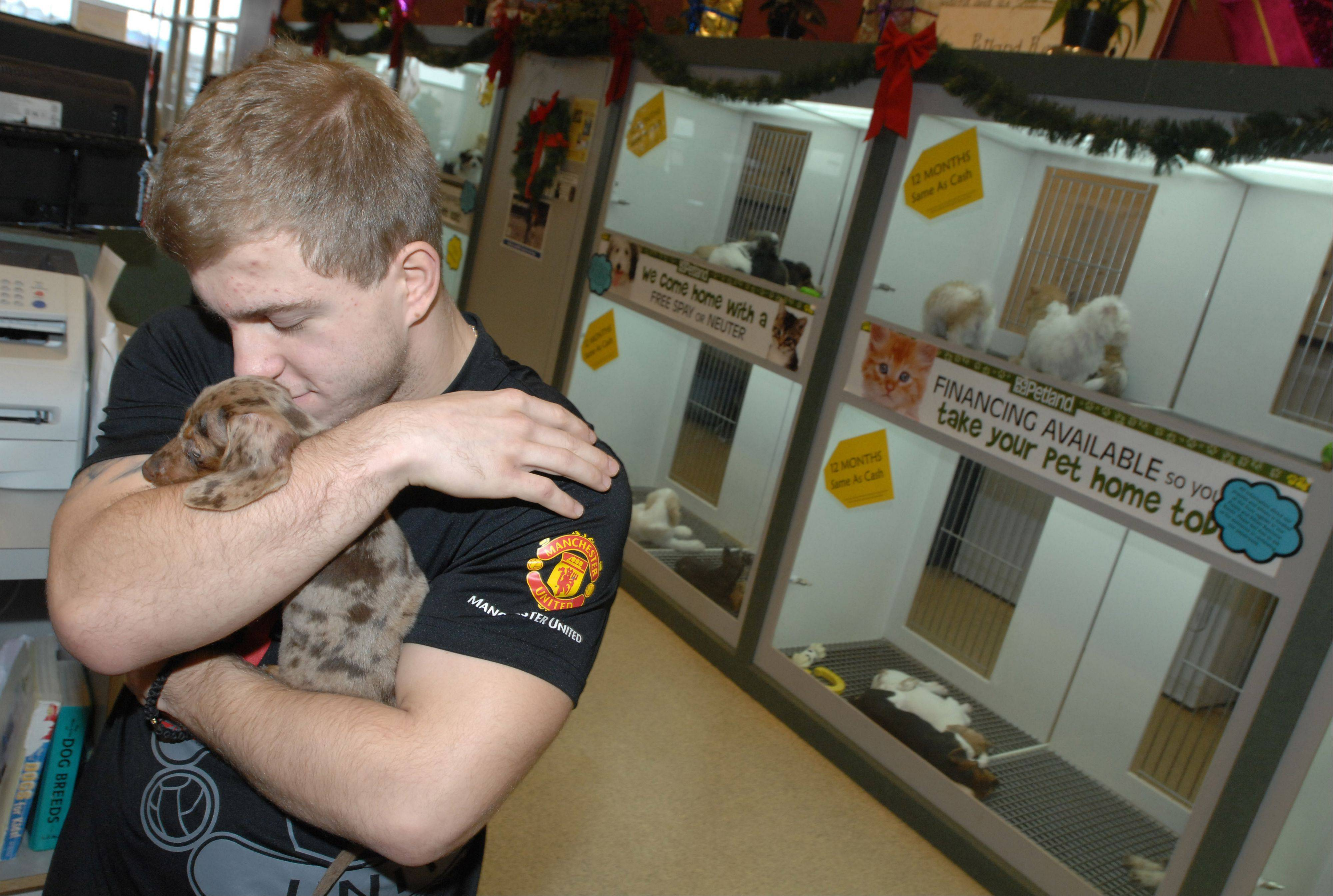 Matt Plackowski hugs a dappled dachshund, which was given to him by Petland Naperville to replace his dog killed in a horrific knife attack.