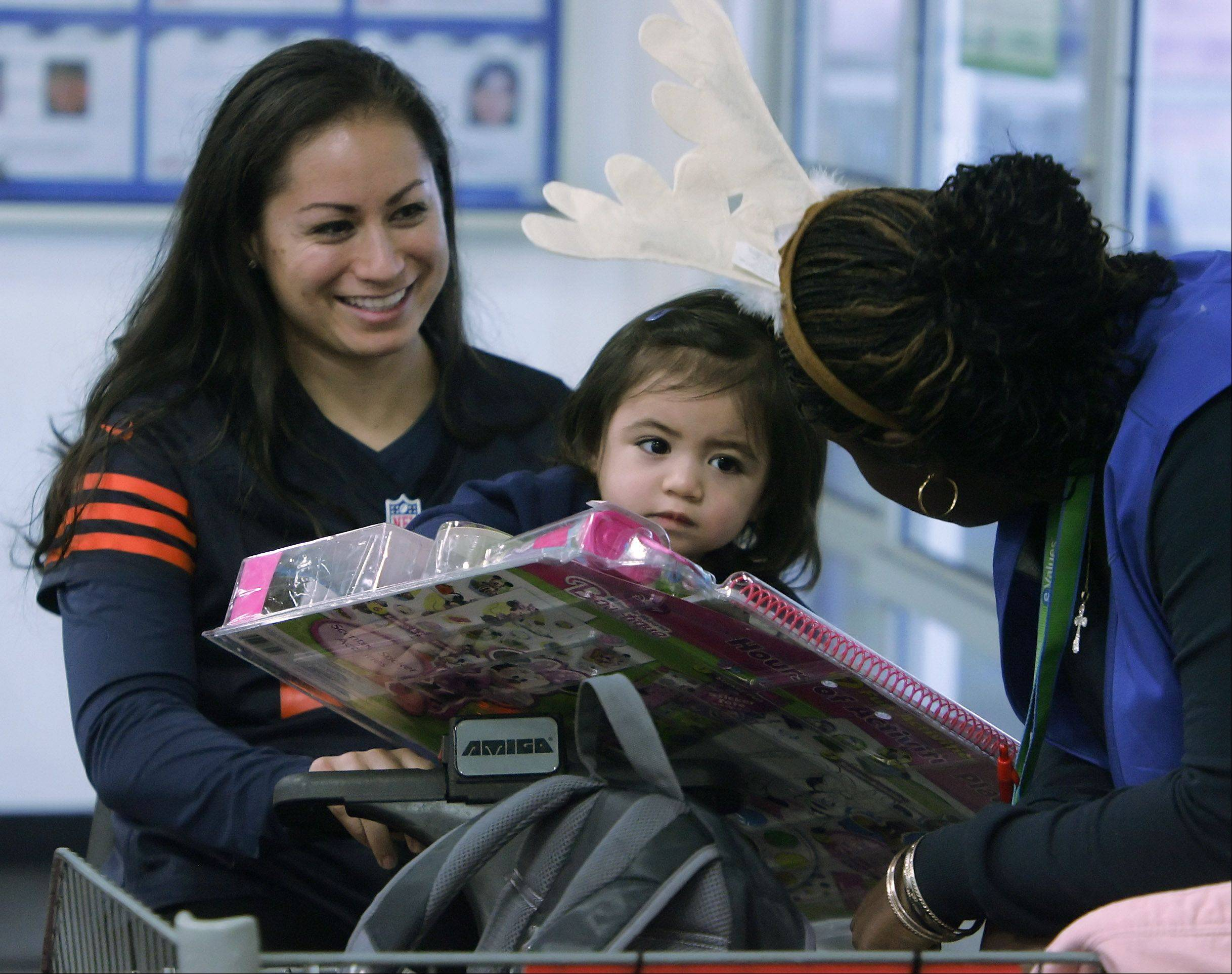 Nicole Toeiana holds her daughter, Mia, 18 months, as they talk to Sam's Club sales associate Mica Stitt while Chicago Bears players' wives shop for clothes, household products, and toys for local families in need at the Sam's Club in Vernon Hills. It's the sixth consecutive year, Sam's Club has teamed with Off The Field, a nonprofit organization comprised of Bears players wives, to help 20 families in the Chicago area selected by the Salvation Army during the holiday season. Nicole is the wife of Bear Matt Toeiana.