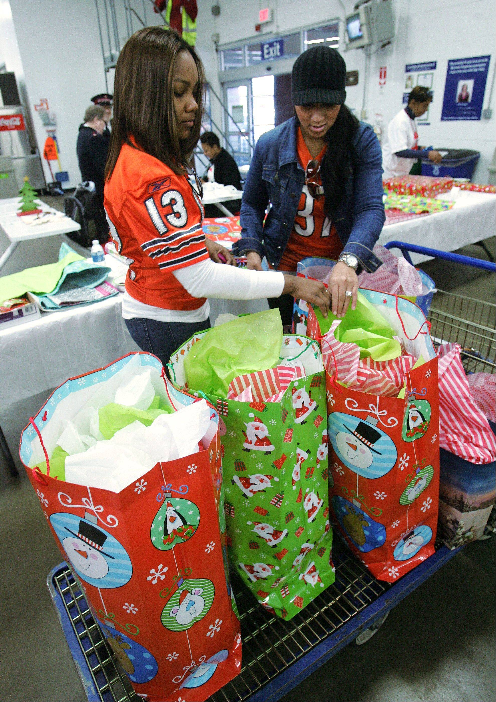 Sanderriqua Knox and Stacey McKie check presents as Chicago Bears players' wives shop for clothes, household products, and toys for local families in need at the Sam's Club in Vernon Hills. Knox's husband is Bears receiver Johnny Knox and Mckie's husband is former Bear Jason McKie.