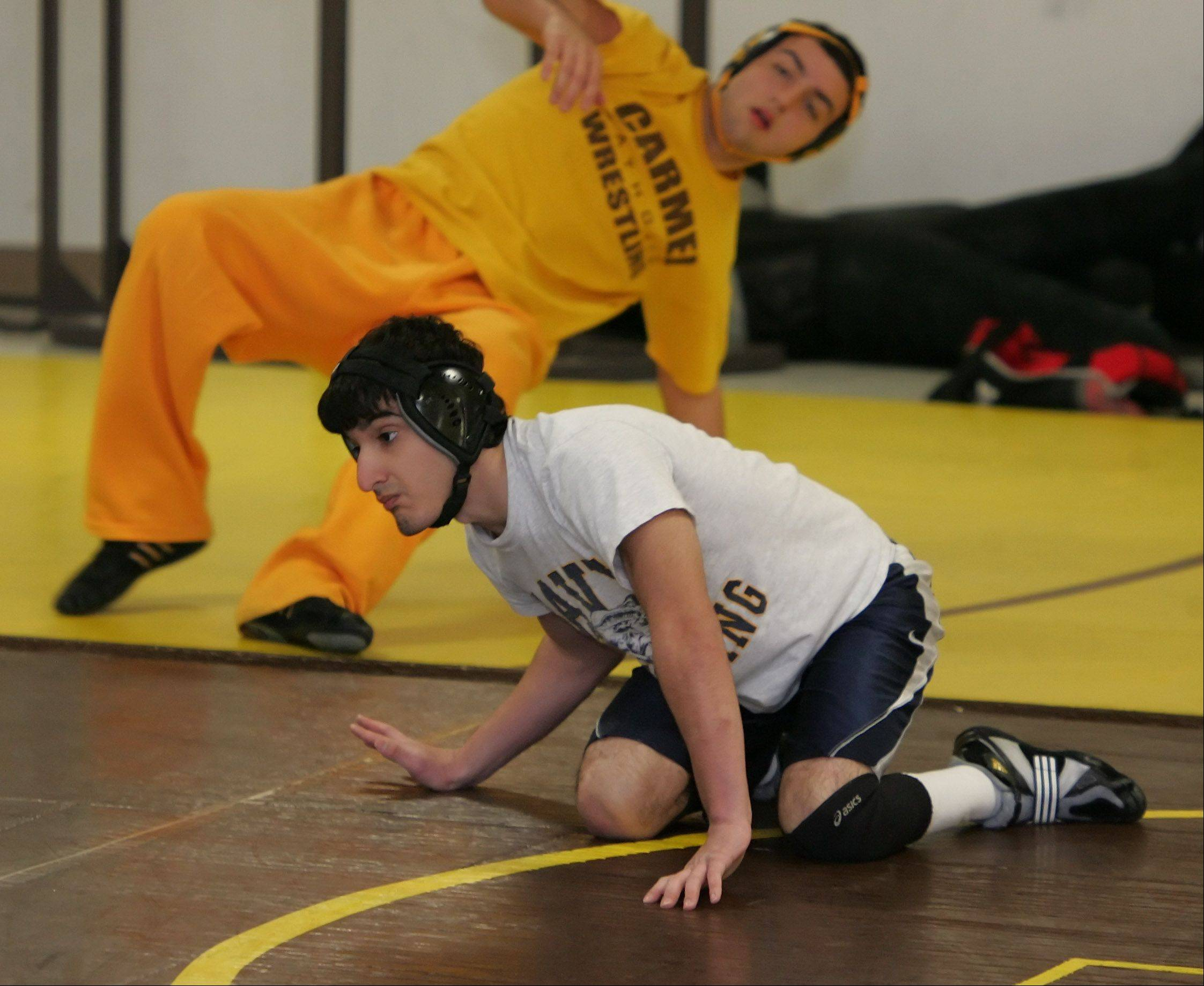 Carmel Catholic's Cristian Migliarese goes through maneuver drills at practice Wednesday. Migliarese, who has spina bifida, nearly quit the sport last season but has won twice by pin already this winter.