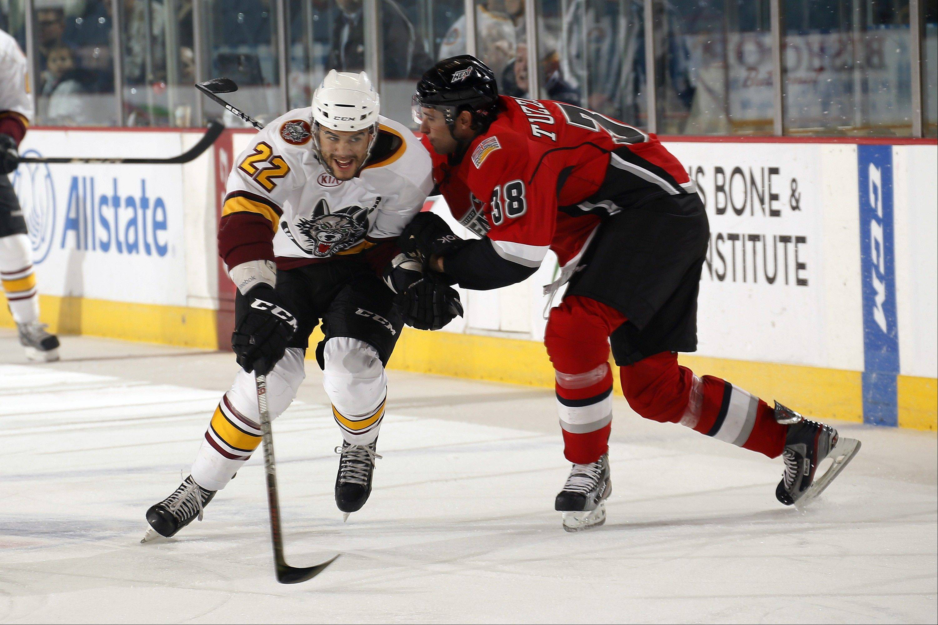 Chicago Wolves winger Darren Archibald battles for position against defenseman Nick Tuzzolino of the Abbotsford Heat. The Wolves earned a 1-0 win in their School-Day game Wednesday afternoon at Allstate Arena.