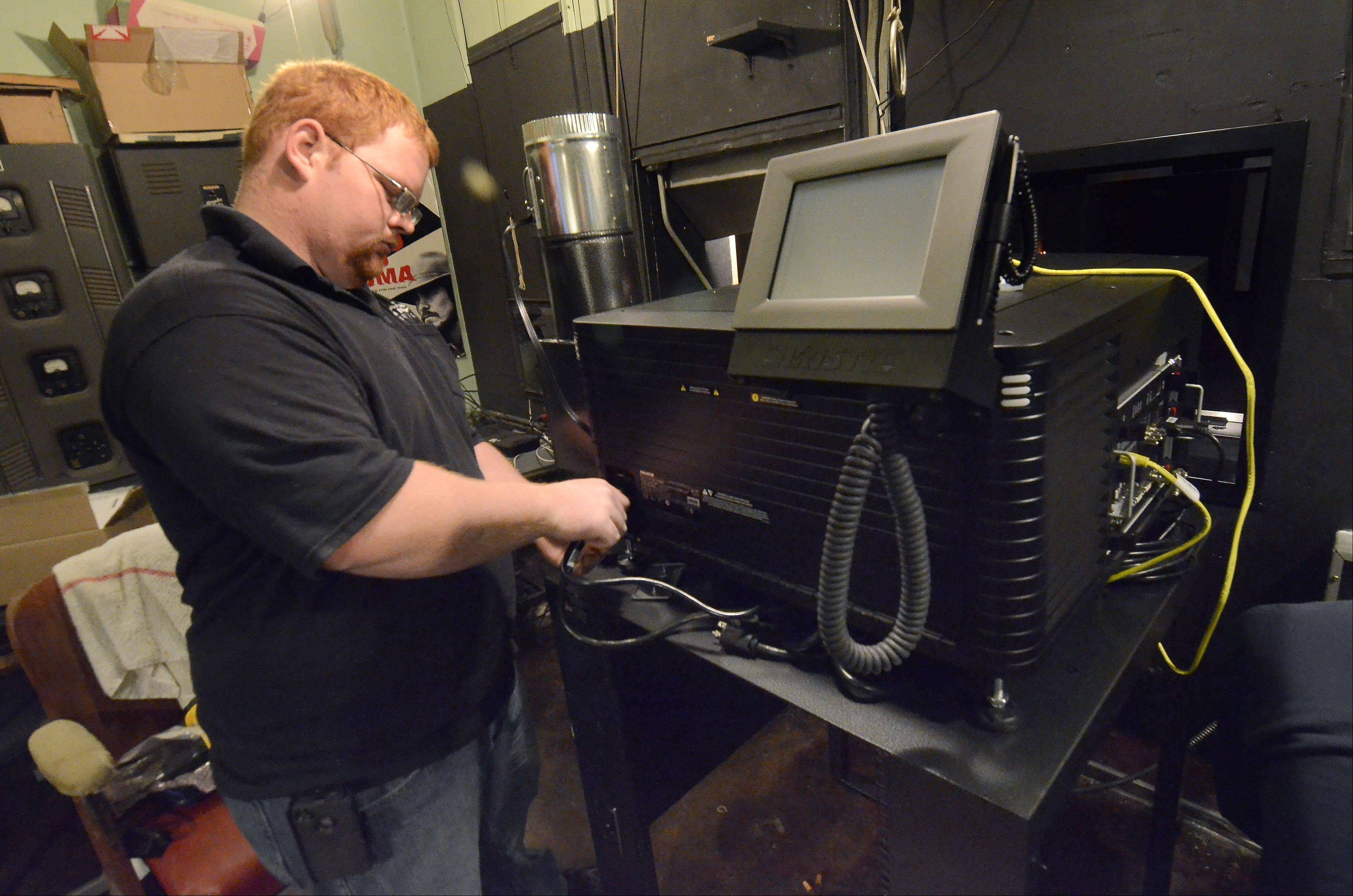 Levi Lampi with Sonic Equipment of Iola, Kan., works on the installation of the new digital projector at the Catlow theater in Barrington. The new projector, which will allow the theater to remain open, was purchased through patron donations.
