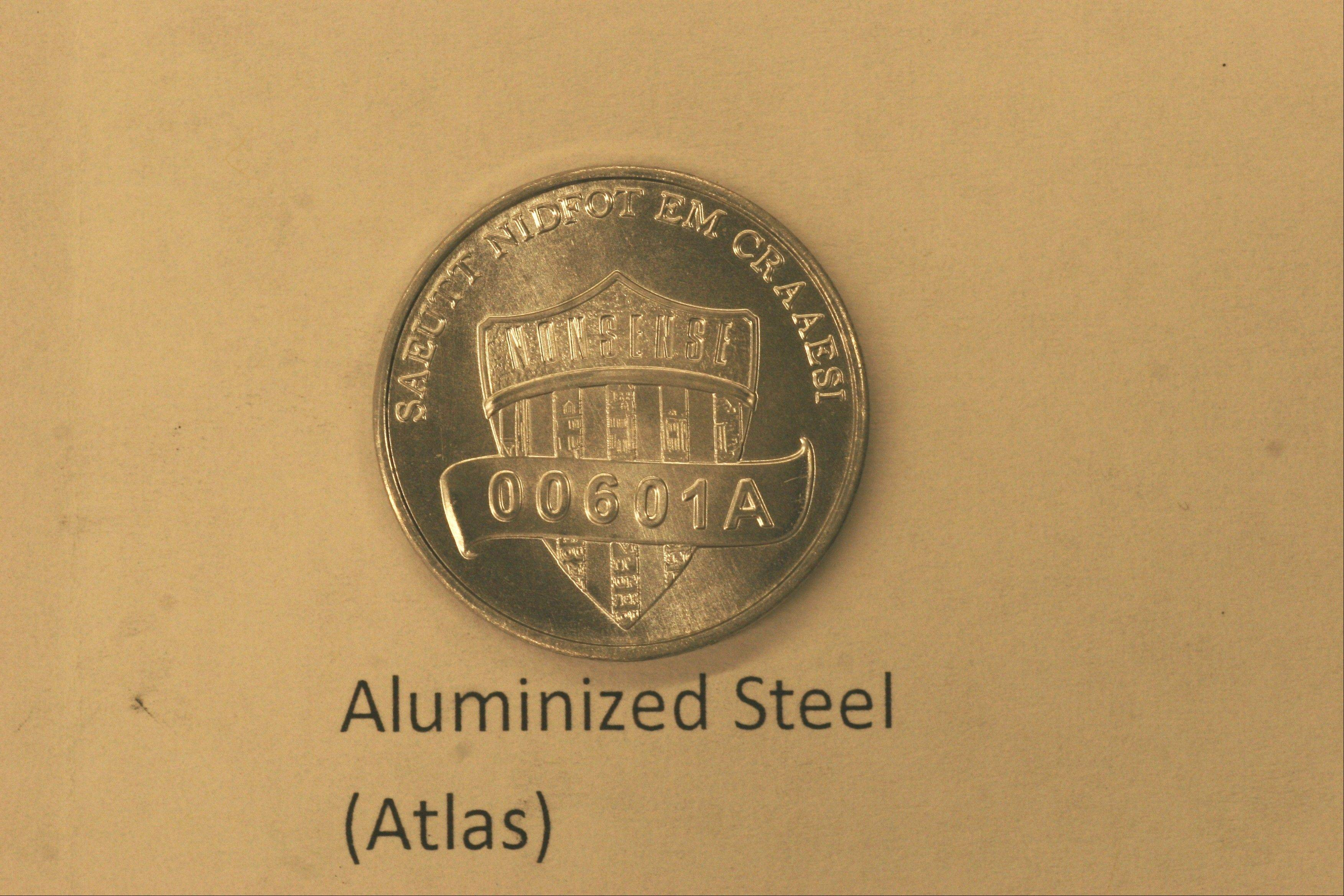 This undated photo provided on Wednesday, Dec. 19, 2012 by the U.S. Mint in Philadelphia shows a nonsense test piece. The Mint has been testing different materials to fiend less expensive ways to make coins.