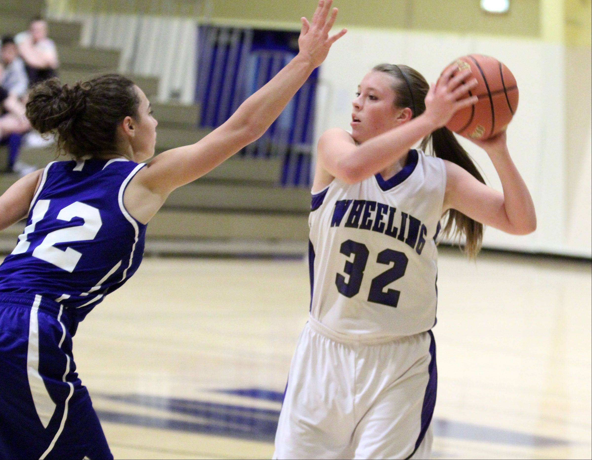 Wheeling�s Brie Majkowski looks to pass over Highland Park defender Tina Berardi.