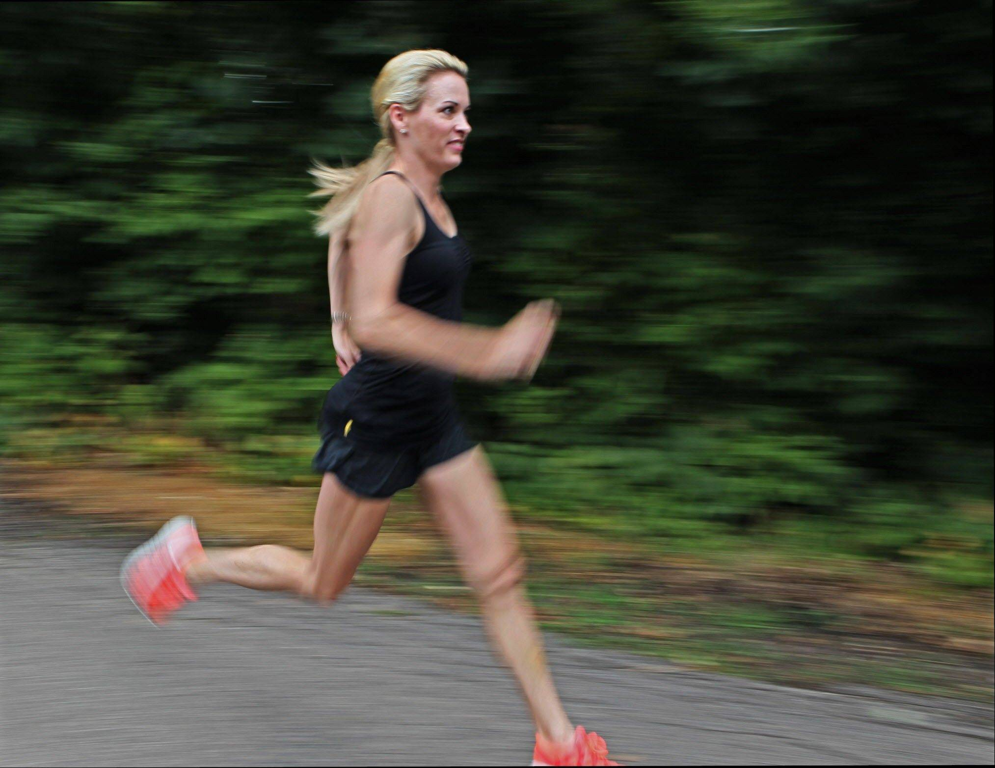 In this photo taken July 19, 2012, Suzy Favor Hamilton runs near her home in Shorewood Hills a suburb of Madison, Wis. The three-time Olympian has admitted leading a double life as an escort. She apologized Thursday after a report by The Smoking Gun website said she had been working as a prostitute in Las Vegas.