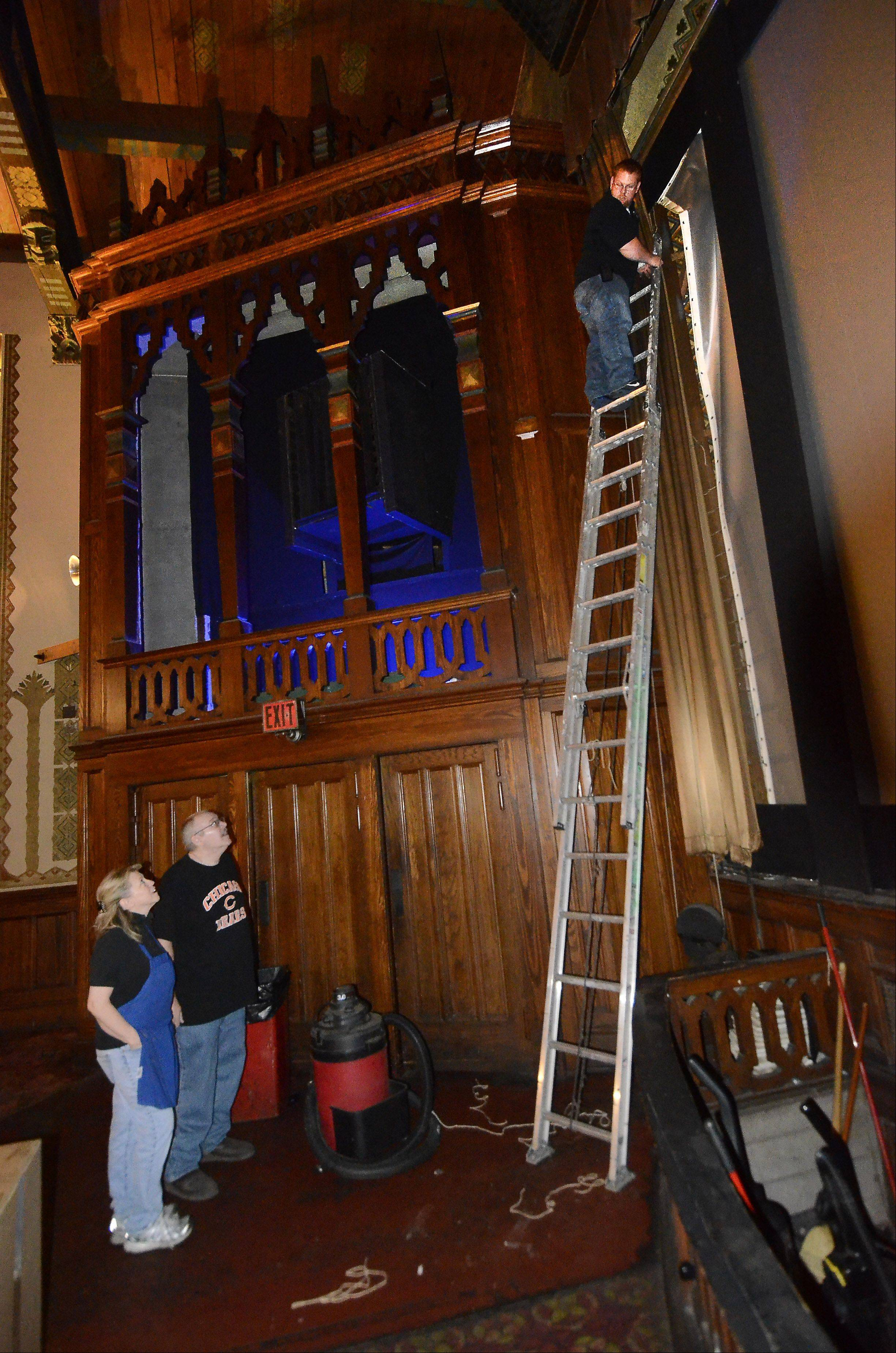 Catlow theater owners Roberta Rapata and Tim O'Connor talk with Levi Lampe as he prepares to install a new speaker near the screen in the historic Barrington theater. The theater also is welcoming a new digital projector purchased largely through patron donations.