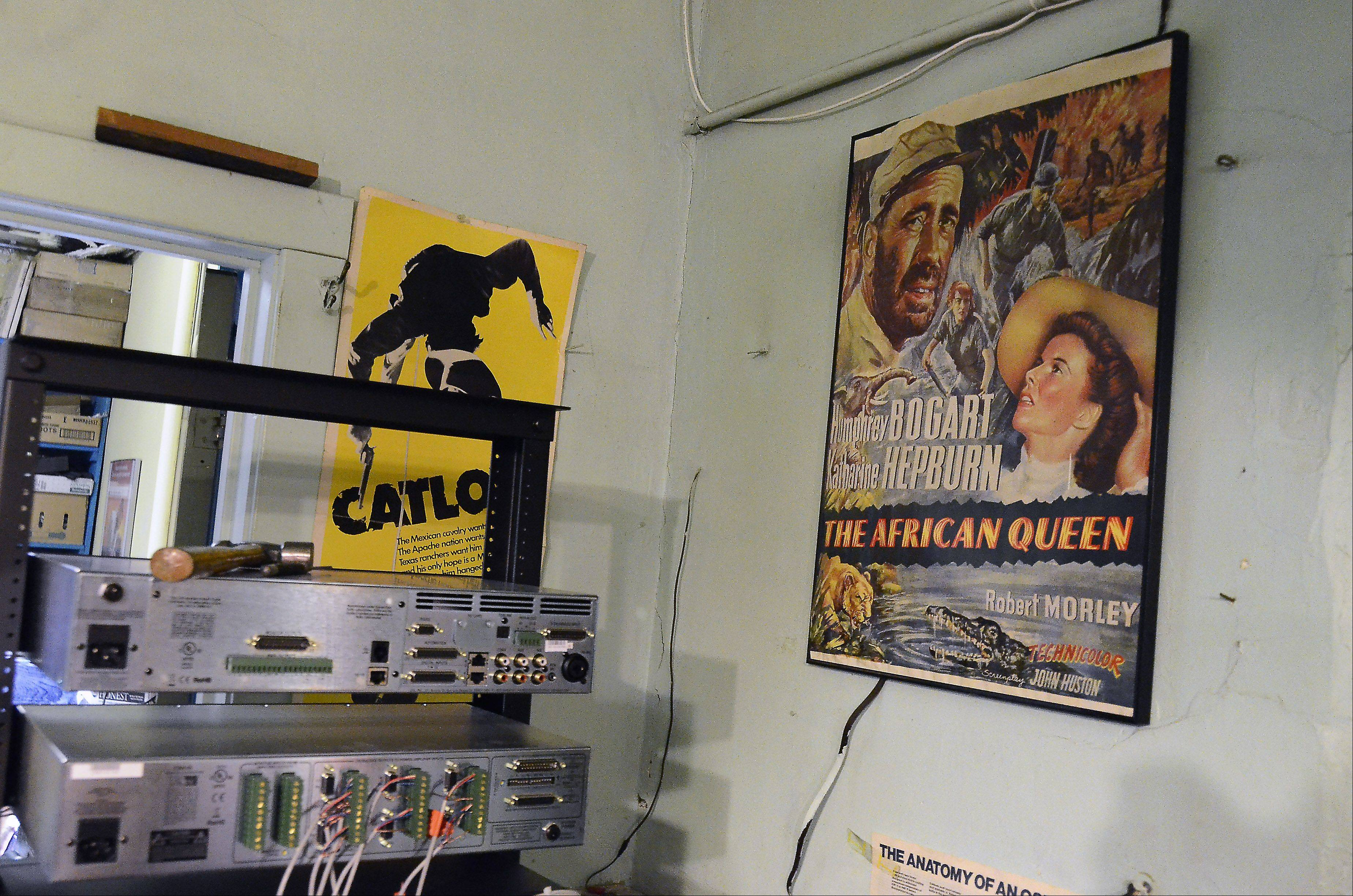 A movie poster for the African Queen from 1951 hangs on the wall next to a rack of new sound equipment in the projection booth at the Catlow theater in Barrington. The theater also is welcoming a new digital projector purchased largely through patron donations.