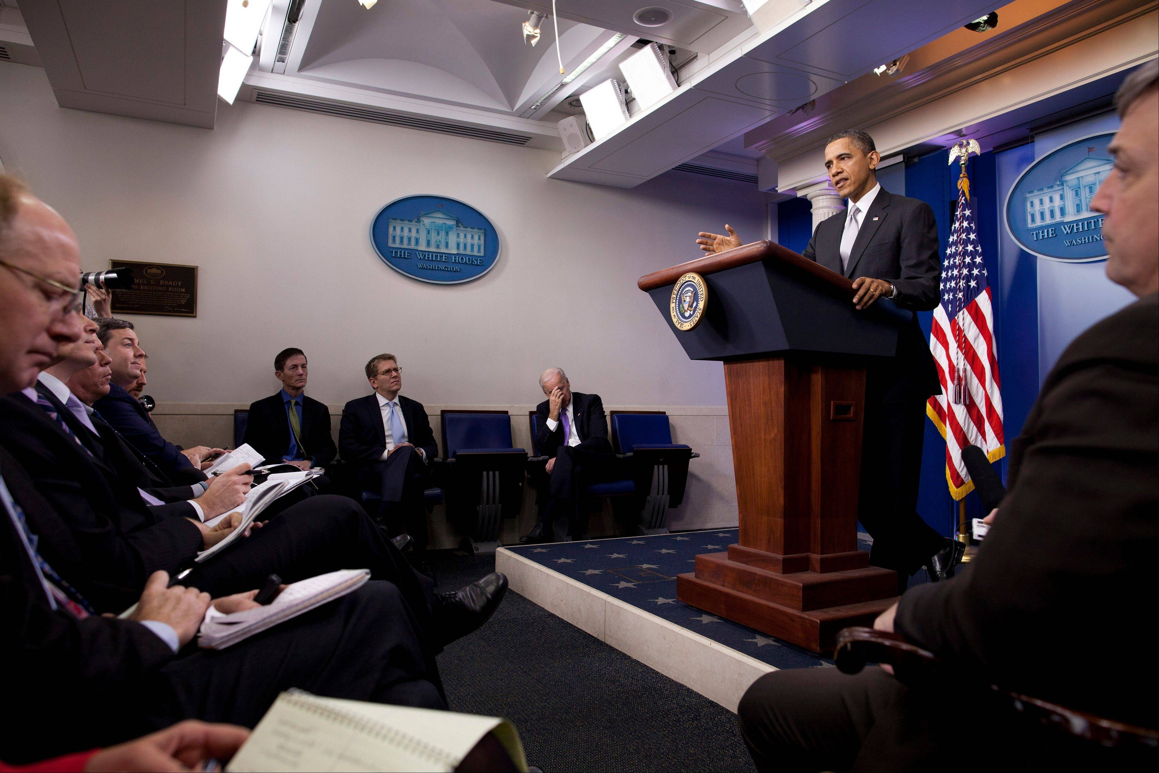 Vice President Joe Biden, third from right, looks down as President Barack Obama gestures as he talks about the fiscal cliff negotiations during a news conference in the briefing room of the White House on Wednesday