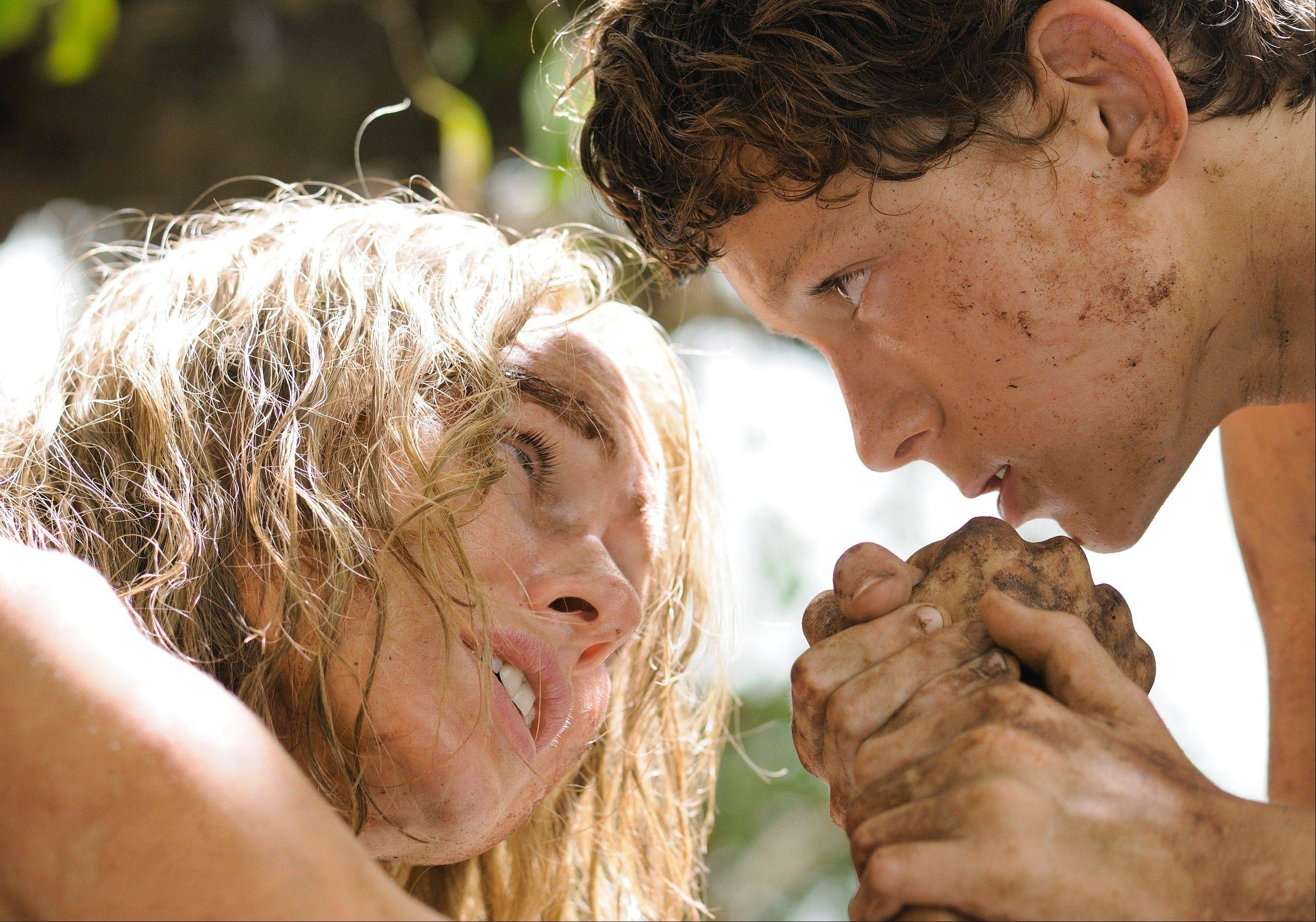 "Lucas (Tom Holland) comforts his wounded mother (Naomi Watts) after they survive a horrific tsunami in the survival thriller ""The Impossible."""