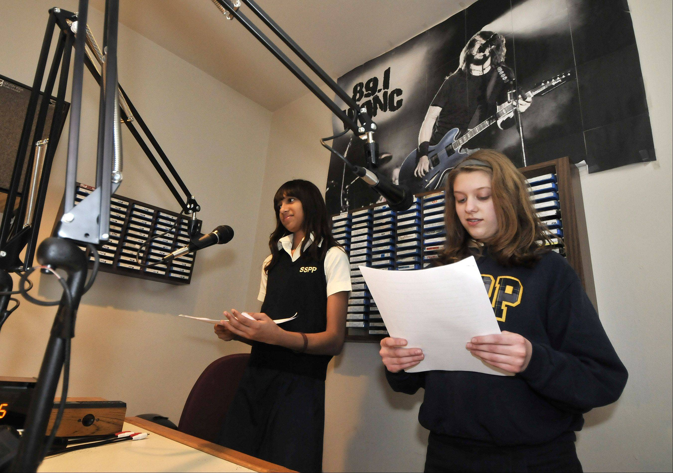 Ss. Peter & Paul School seventh-graders Shirley Armstrong and Lara Skarbek read their lines at WONC studios in Naperville.