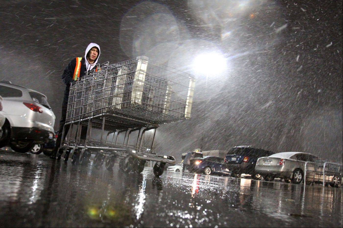 Kevin Kurzawski collects shopping carts as snow first starts to fall, at the Jewel store at Randhurst Mall in Mount Prospect on Thursday.