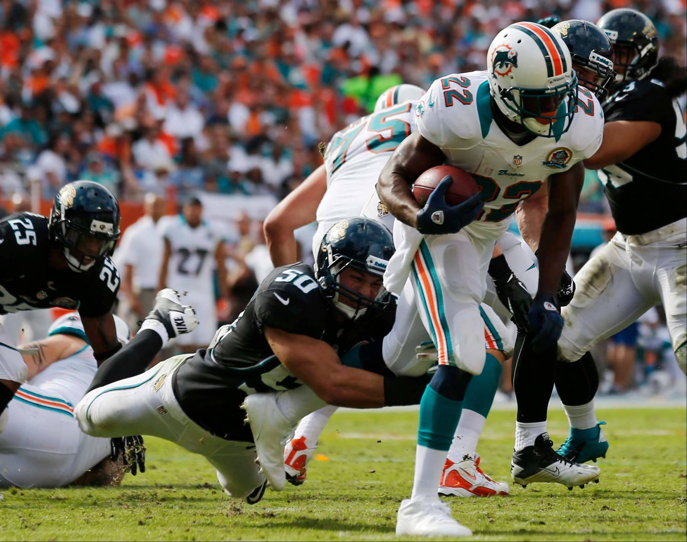 Miami Dolphins running back Reggie Bush (22) runs as Jacksonville Jaguars outside linebacker Russell Allen (50) holds on to his leg during the first half of an NFL football game on Sunday, Dec. 16, 2012, in Miami.