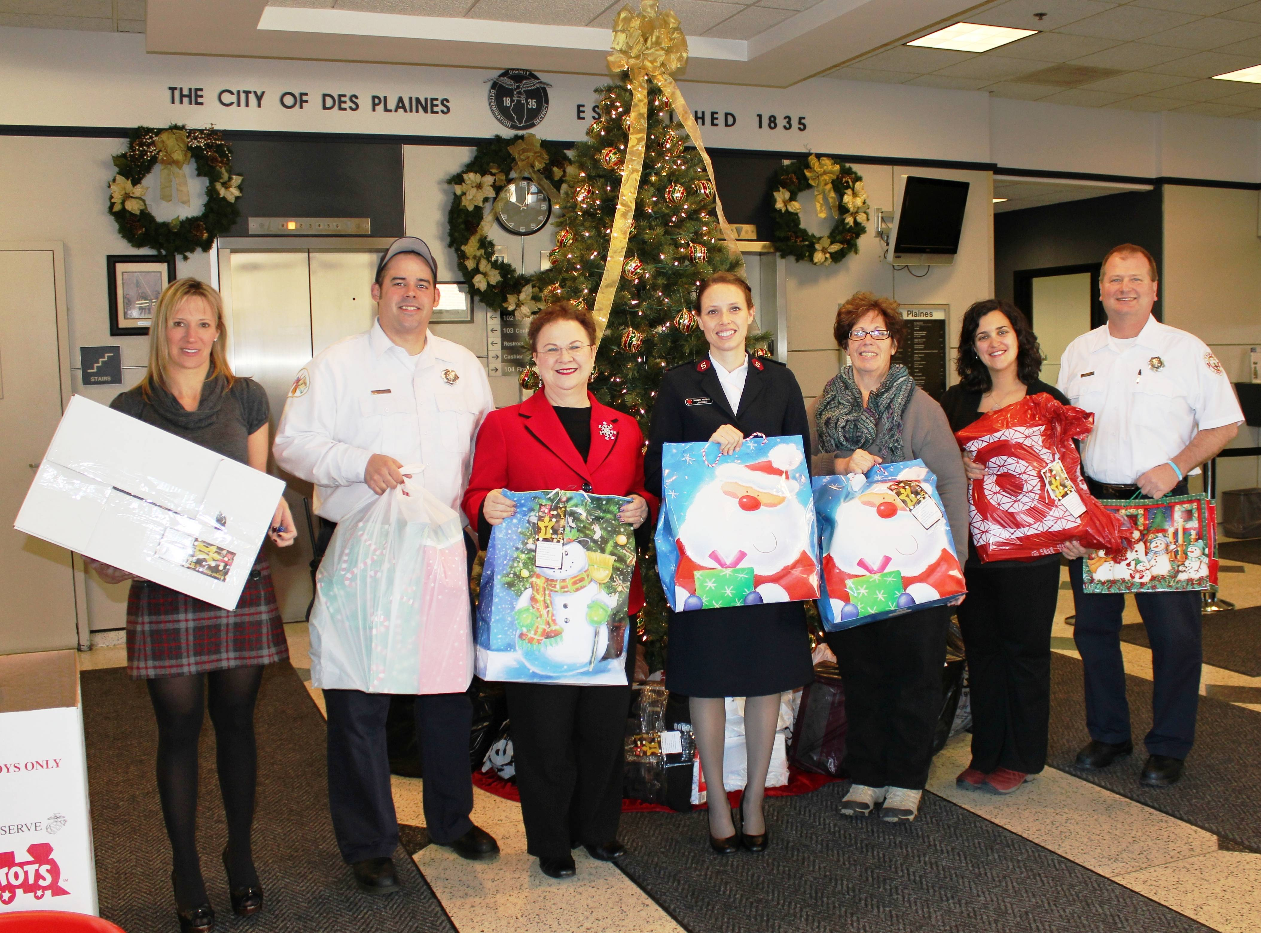(pictured above left to right) Des Plaines Fire Prevention Bureau Secretary Mary Nistler, Firefighter/Paramedic Ed Rogers, City Clerk Gloria J. Ludwig, Salvation Army Lieutenant Shannon Martinez, Community Health Nurse Kathy Puetz, Des Plaines Community Social Worker Jeanine Stricker and Fire Department Lieutenant Ken Palenik pose for a photograph with some of the many gifts donated to the Salvation Army's Angel Tree Program.