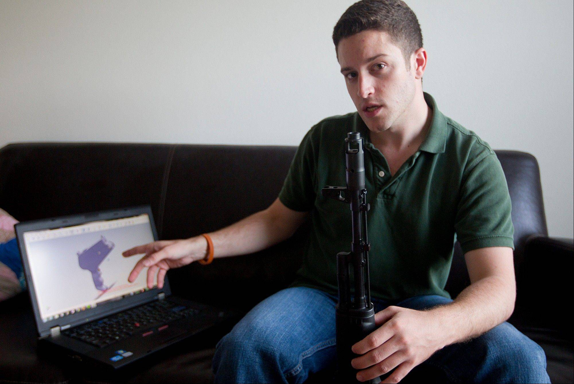"""Wiki Weapons"" project leader Cody Wilson points to his laptop screen displaying an image of a prototype plastic gun on the screen, while holding in his other a weapon he calls ""Invivdual Mandate,"" in Austin, Texas."