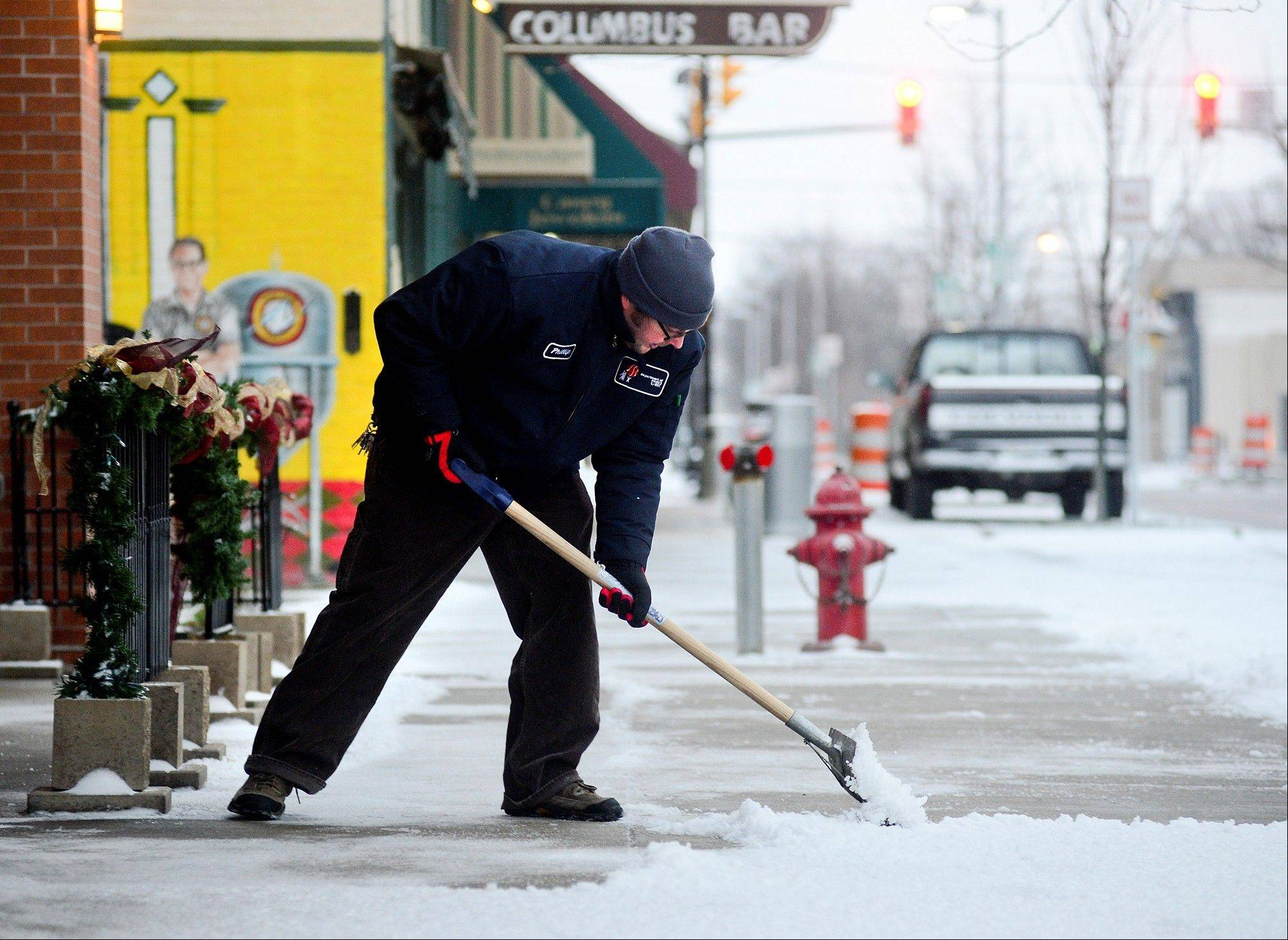Department of Parks and Recreation employee Phillip Forney shovels snow and ice Friday in downtown Columbus, Ind.