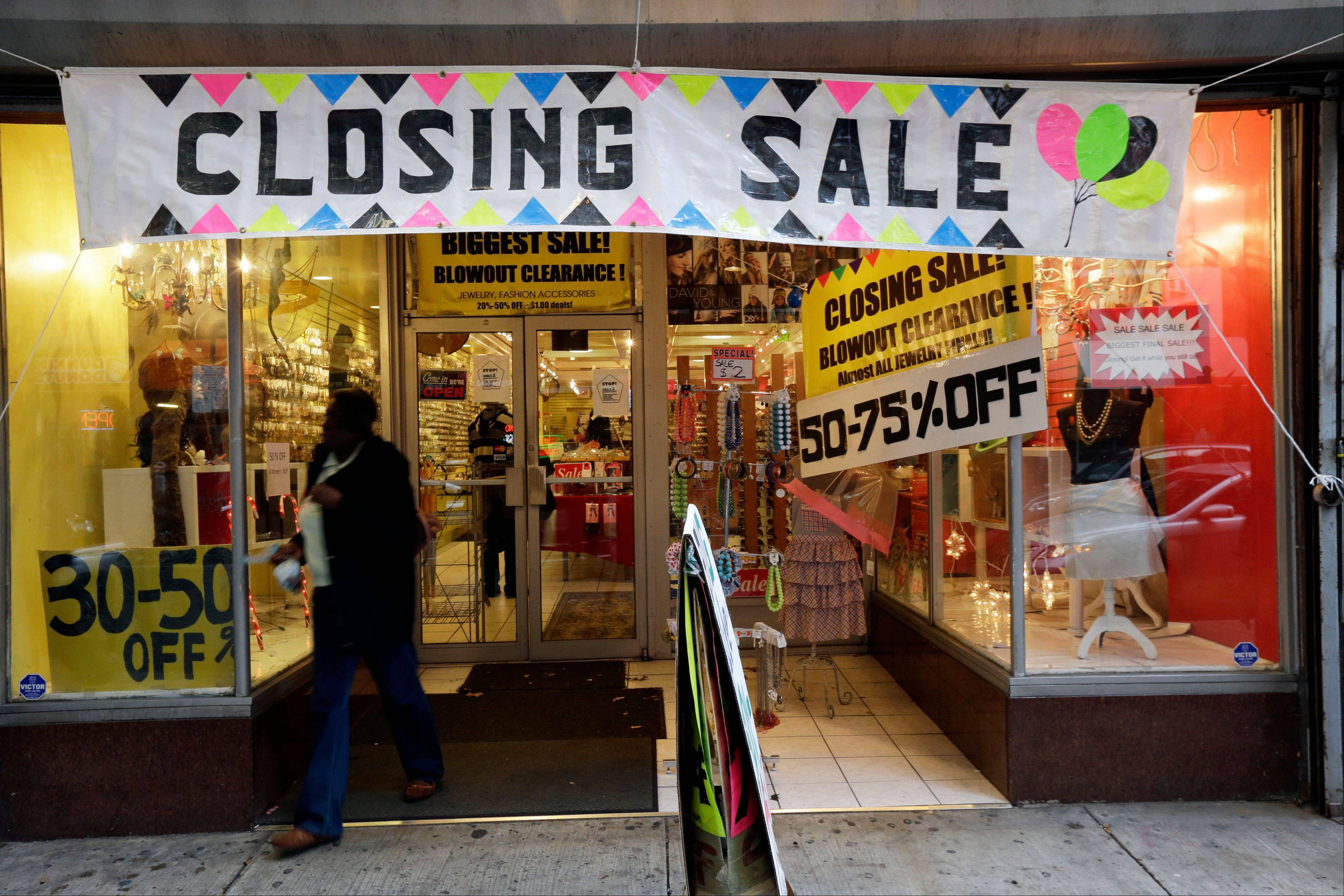 "A person exits a business Tuesday with a ""Closing Sale"" sign, in Philadelphia. Spending has continued despite confidence among consumers sinking to its lowest point since July."