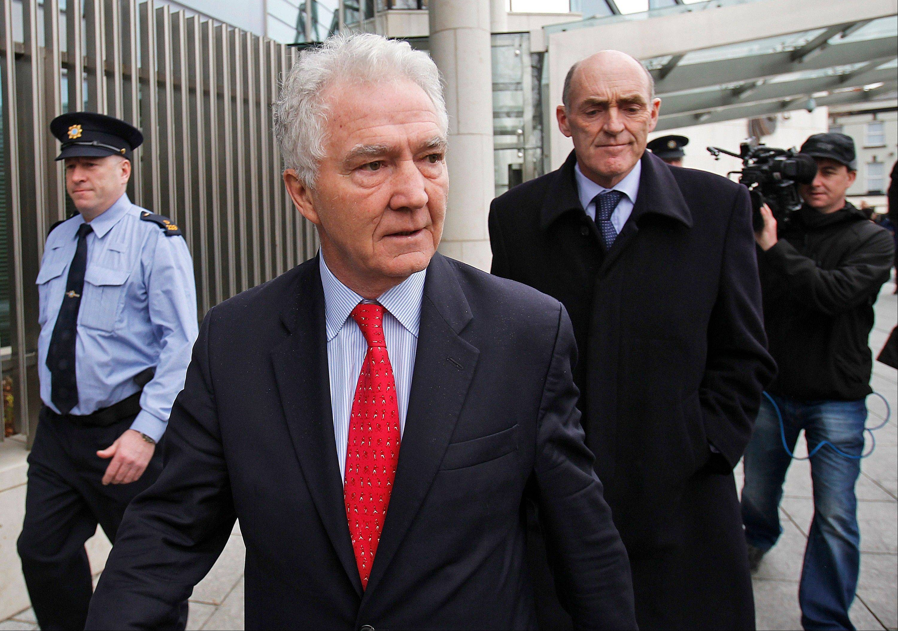 Former Anglo Irish Bank chief executive and chairman Sean FitzPatrick, front center, leaves District Court, in Dublin, Ireland, after being given bail appearing on charges of giving auditors false or misleading information on directors' loans over a five-year period, Friday Dec. 21, 2012. The 64-year old former chief of Ireland's collapsed Anglo Irish Bank, FitzPatrick, has been arraigned Friday on fraud charges of misleading auditors and shareholders alleging over $180 million in personal loans.
