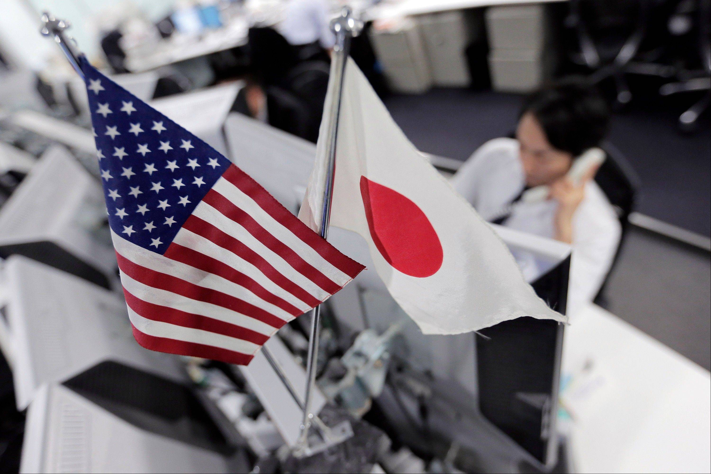 Money traders work under flags of the United States and Japan at a foreign exchange firm in Tokyo Friday.