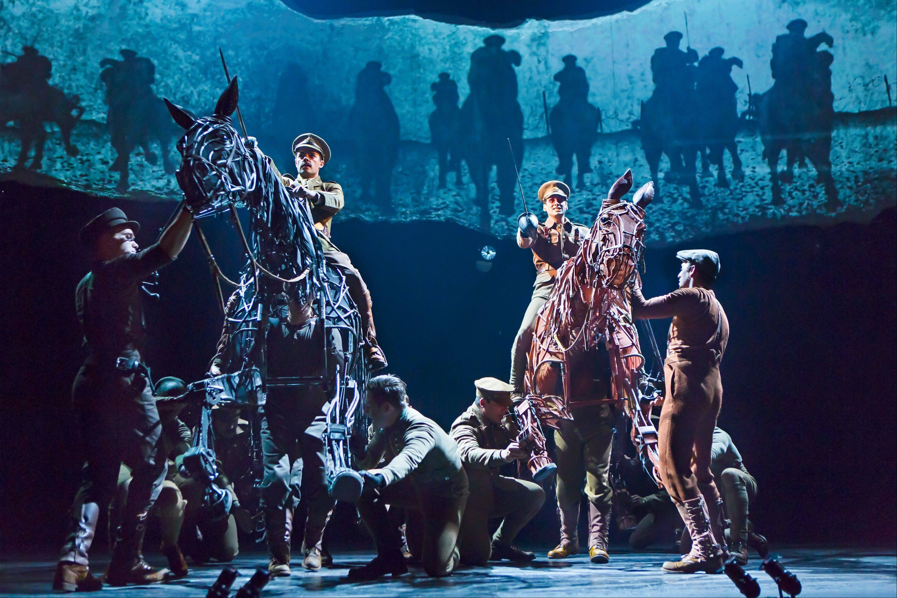 "Soldiers (Grayson DeJesus riding black horse Topthorn and Michael Wyatt Cox riding Joey) do battle in the North American tour of ""War Horse,"" which plays Chicago's Cadillac Palace Theatre through Saturday, Jan. 5."