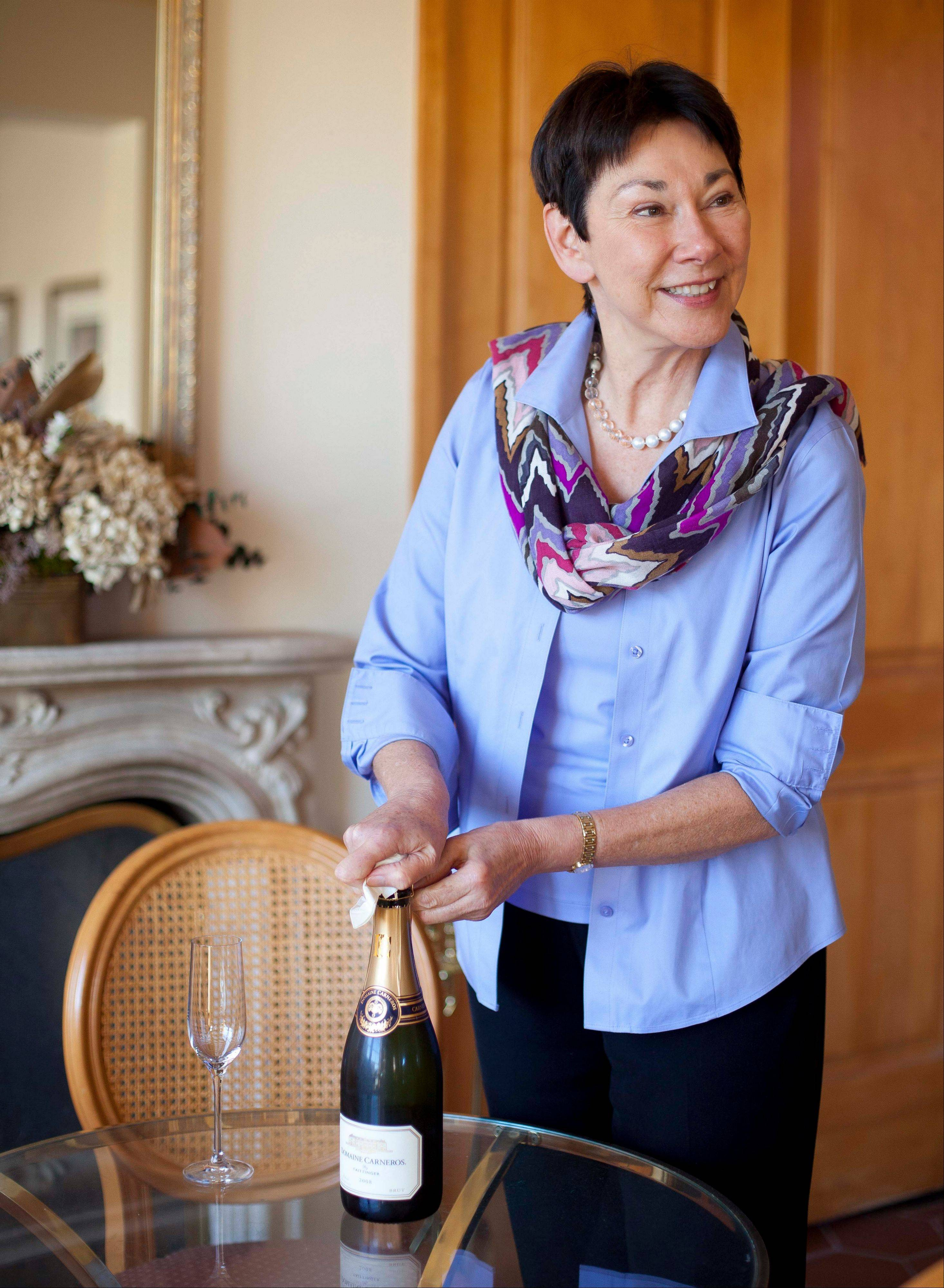 CEO and winemaker Eileen Crane opens a bottle of Brut Cuvee sparkling wine at Domaine Carneros in Napa, Calif. She's a fan of using sparkling wine is cocktails.