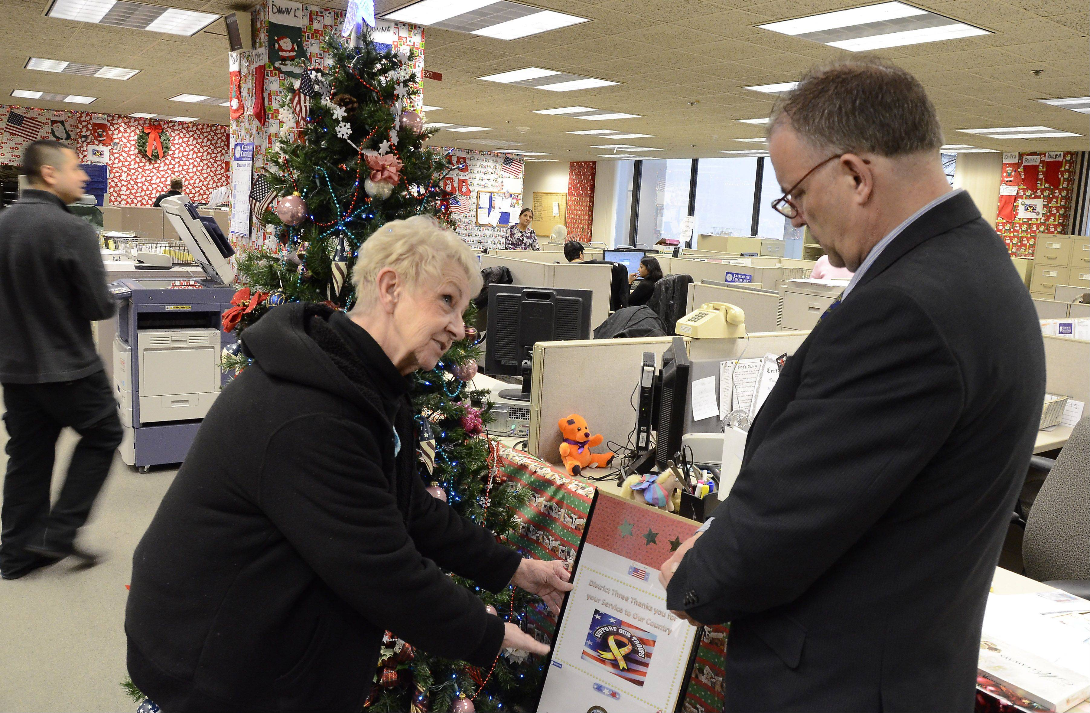 Bill Zars/bzars@dailyherald.comJoan Tessman talks with co-worker Bob Schultz about his holiday decorations at the Clerk of the Circuit Court of Cook County office at the Third Municipal District Courthouse in Rolling Meadows.