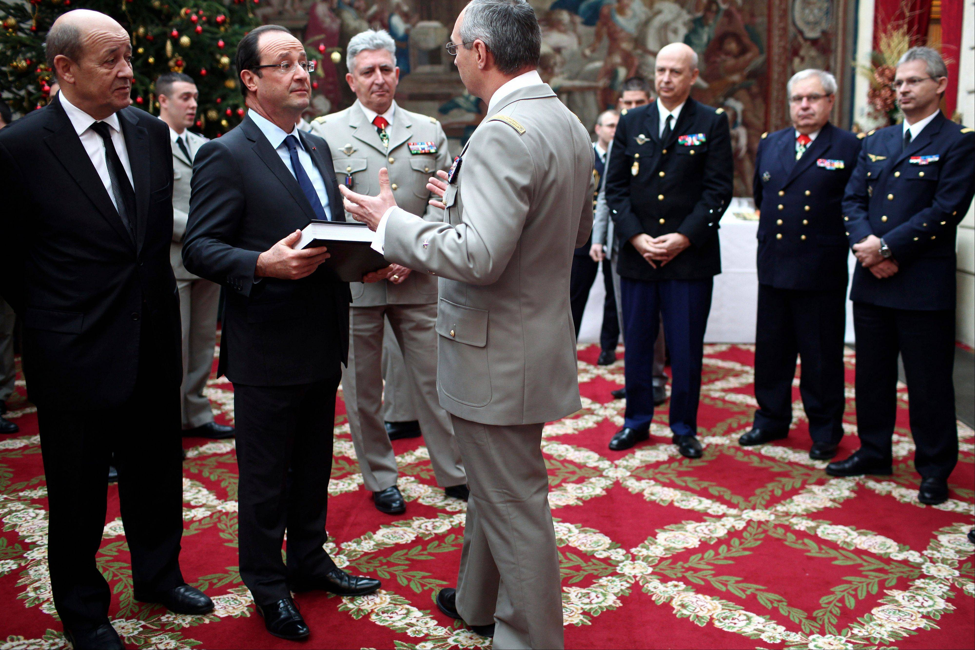 "France's President Francois Hollande, second left, and France's Defense Minister Jean YvesLe Drian, left, talk with French army General Eric Hautecloque Raysz, center, during a ceremony to honor French troops home from Afghanistan, at the Elysee Palace, in Paris, Friday, Dec. 21, 2012. Hollande has declared ""mission accomplished"" for French combat troops who returned home recently from Afghanistan. France still has 1,500 troops in Afghanistan repatriating equipment or working in roles like providing medical care or helping run Kabul's airport. Hollande said the numbers will decline to 500 by mid-2013."