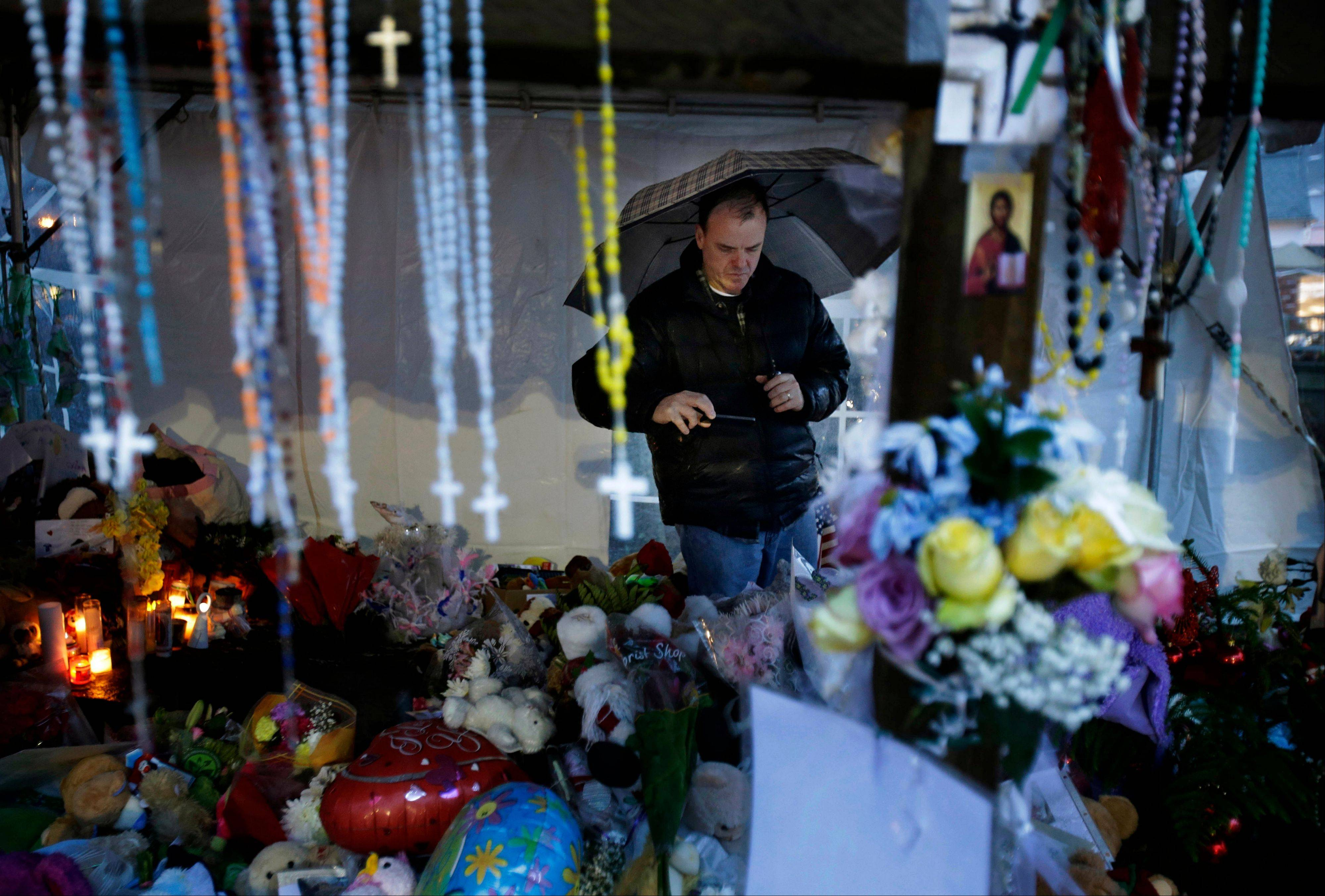 Ben Toby of Sandy Hook visits a memorial to the Newtown shooting victims during a heavy rain in the Sandy Hook village of Newtown, Conn., Friday, Dec. 21, 2012. The shooter, Adam Lanza, walked into Sandy Hook Elementary School in Newtown, Dec. 14, and opened fire, killing 26 people, including 20 children, before killing himself.