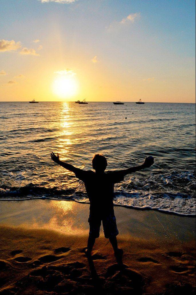 A boy celebrates on a Florida beach at sunset this past summer.