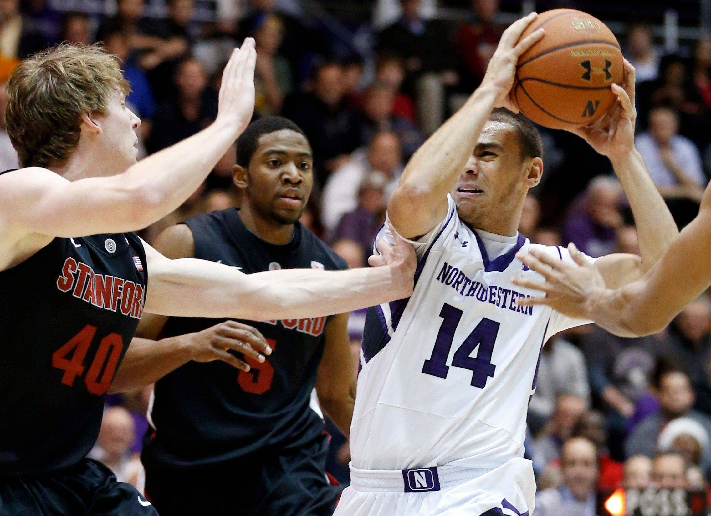 Northwestern guard Tre Demps (14) drives to the basket as Stanford forward John Gage (40), guard Chasson Randle and forward Josh Huestis, right, defend Friday during the second half. Stanford won 70-68.