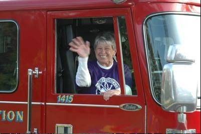 Principal Marcella Bosnak rides high in the Newport Township firetruck to lead the school parade. The 29th annual Jog-a-thon raised $32,000 for the school's Scholarship Fund.