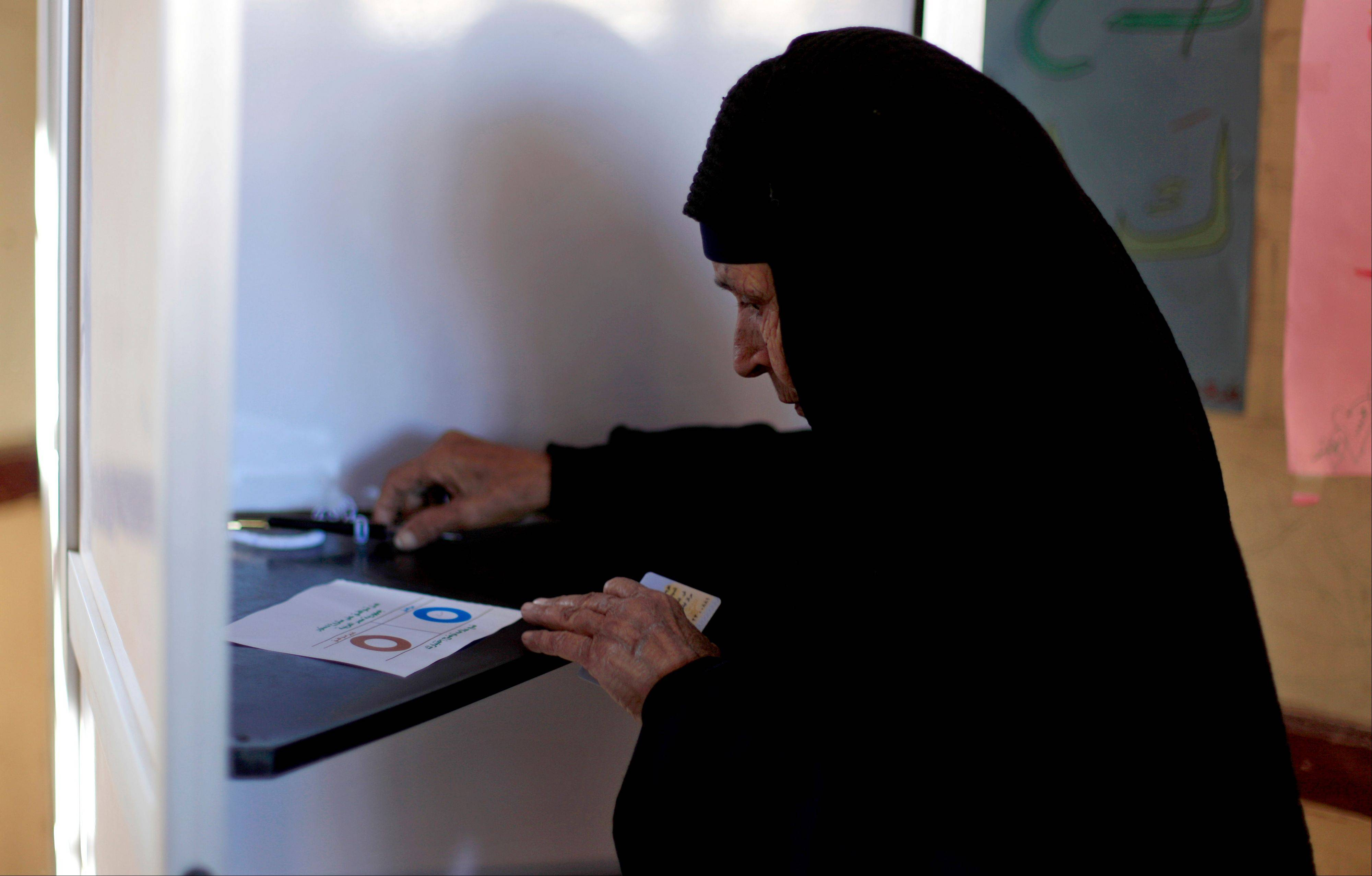 An Egyptian woman casts her vote Saturday during the second round of a referendum, just south of Cairo, Egypt.