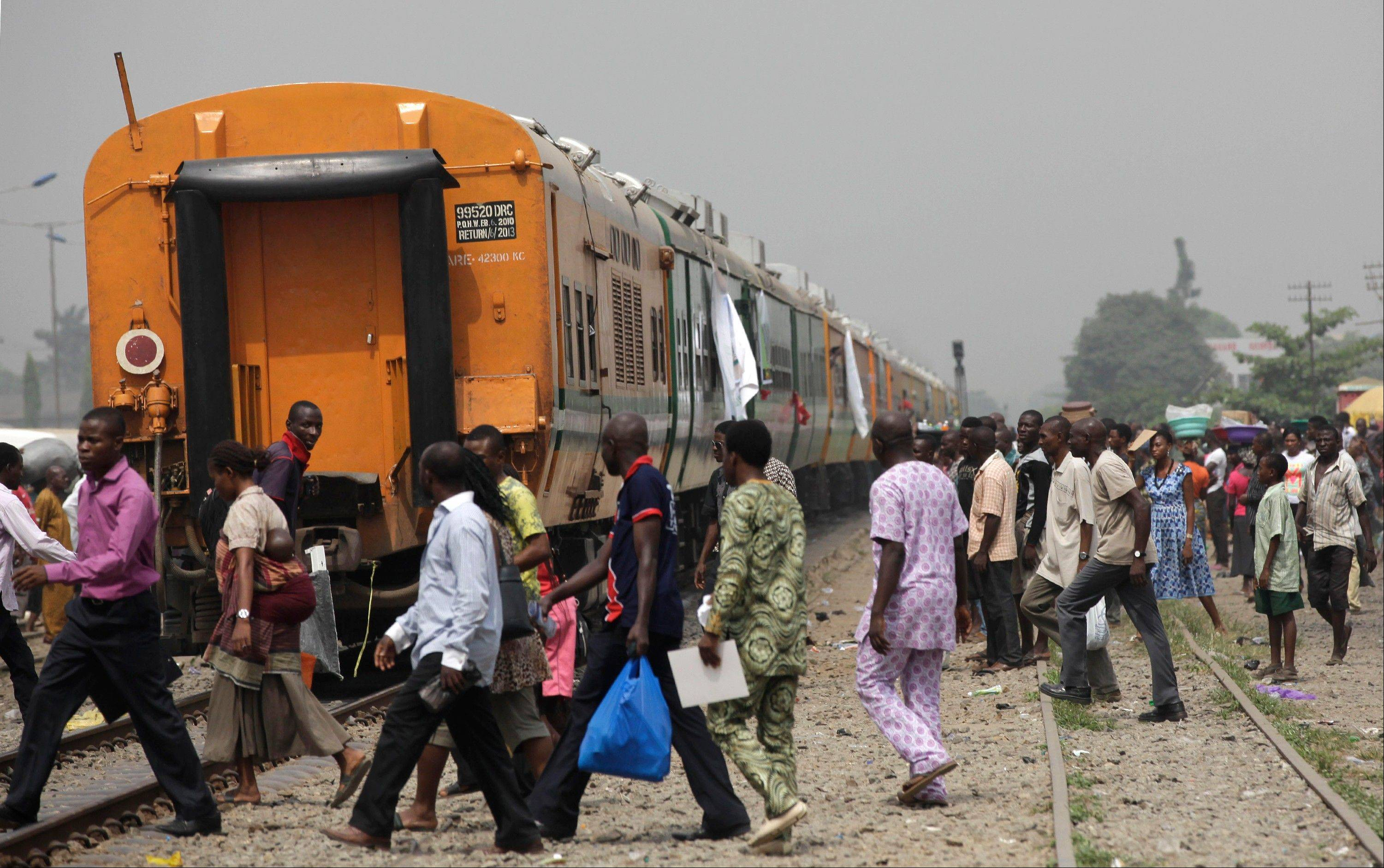People cross the tracks Friday as they wait for the train to move off as part of a newly inaugurated train service to Kano, Nigeria, in Lagos, Nigeria.