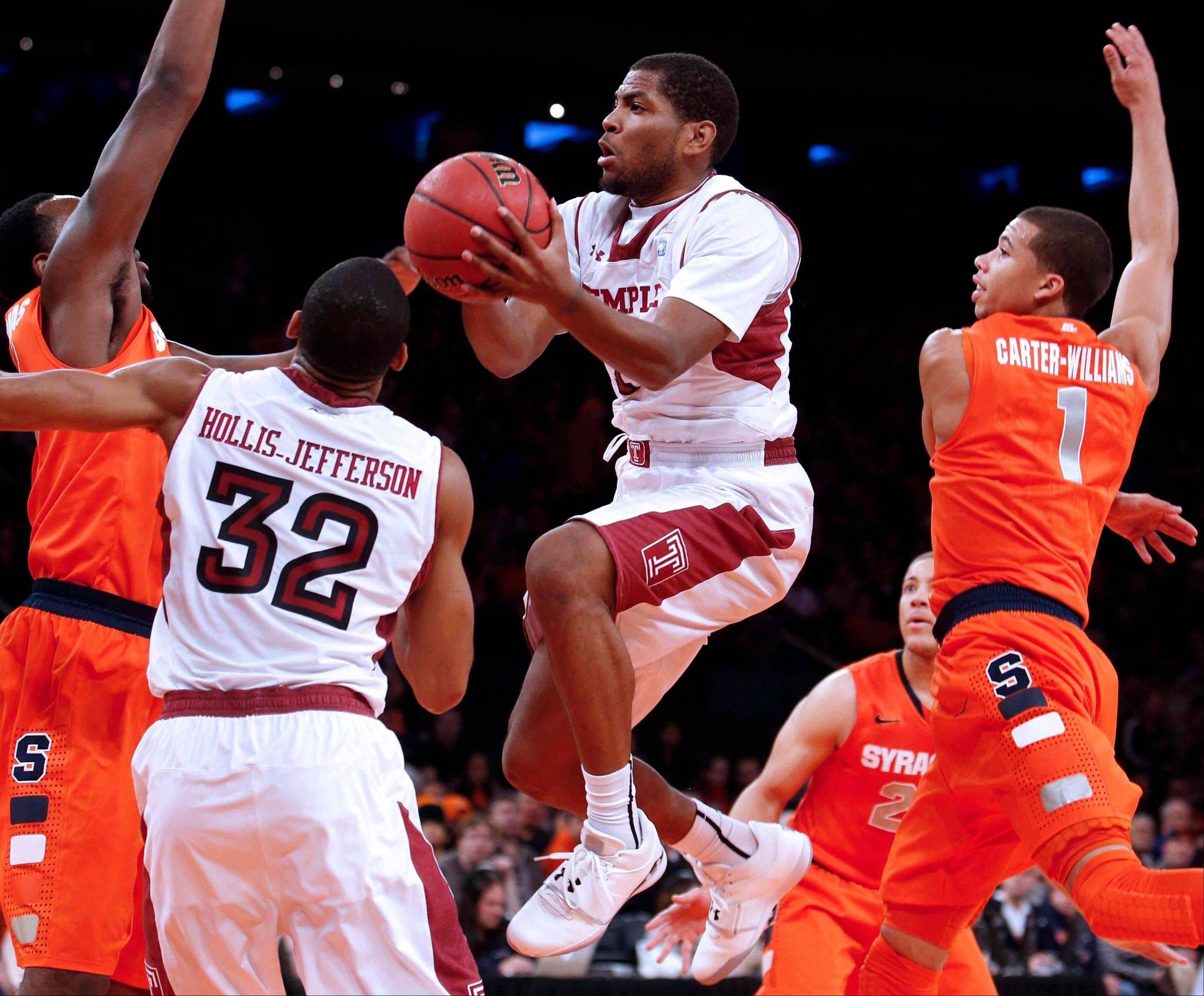 Temple�s Khalif Wyatt shoots against Syracuse�s Rakeem Christmas, left, and Michael Carter-Williams (1) during the first half in the Gotham Classic tournament at Madison Square Garden, Saturday in New York. Temple defeated Syracuse 83-79.