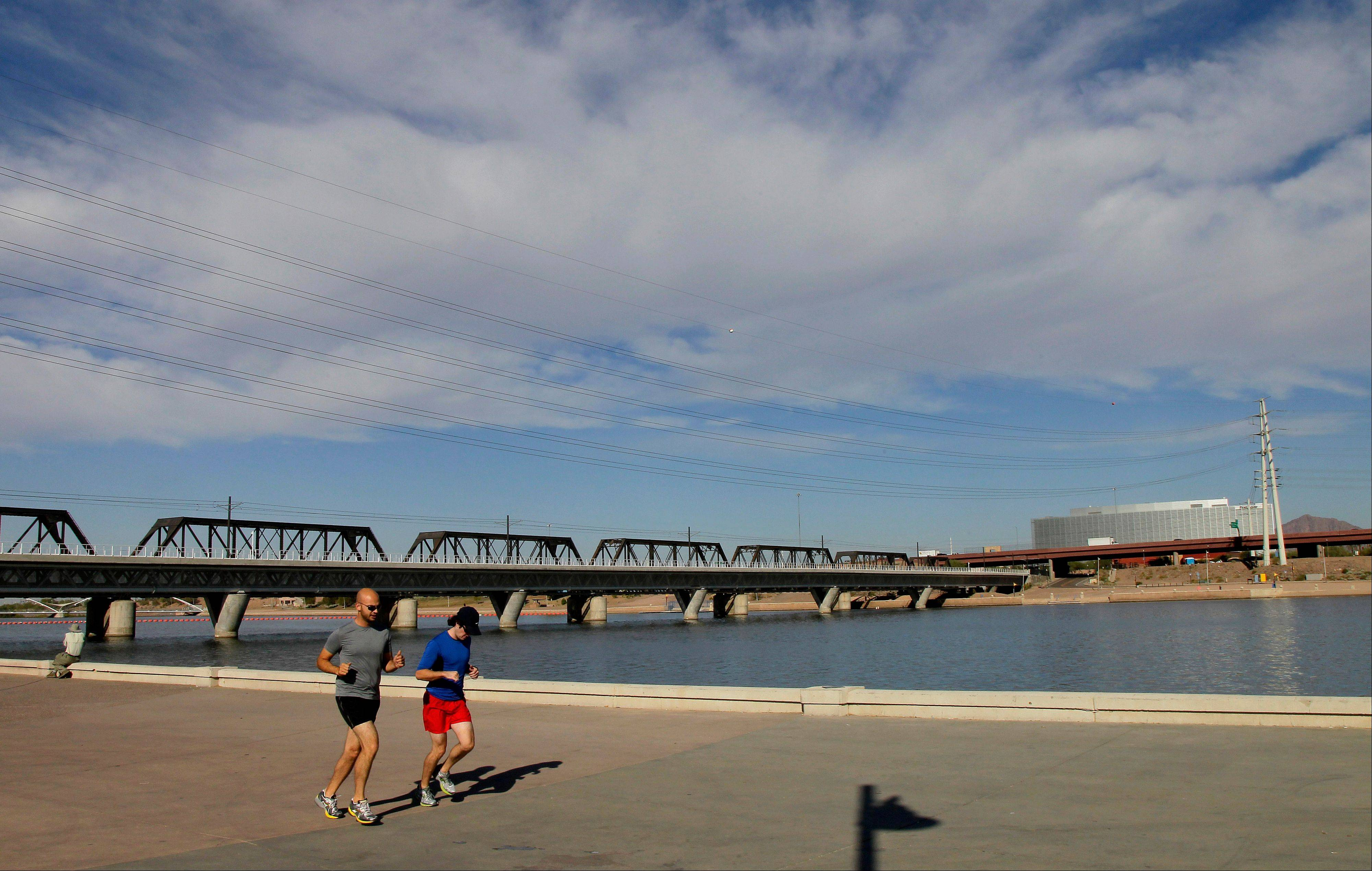 A couple jogs along Tempe Town Lake in Tempe, Ariz.
