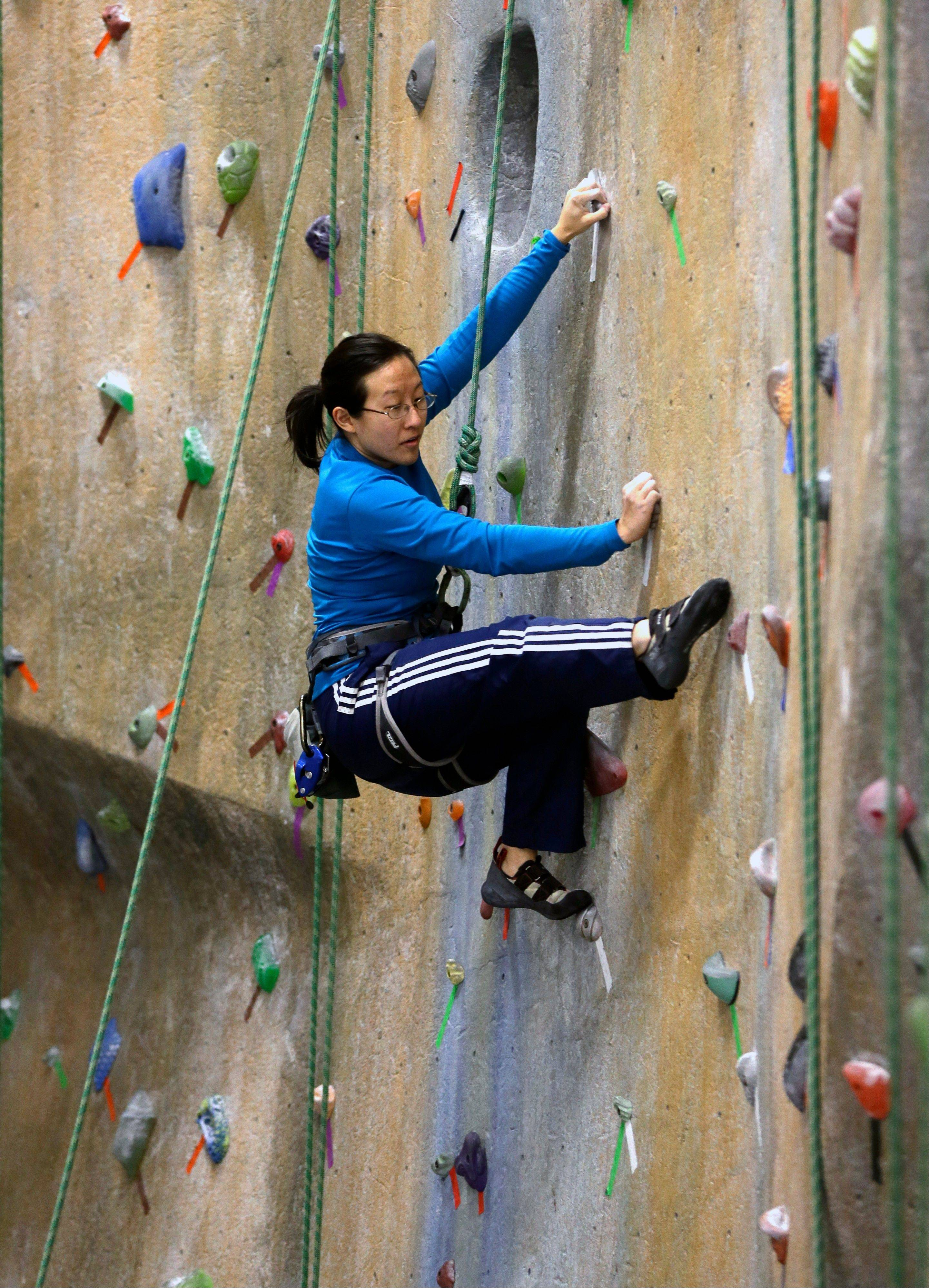 Joyce Lu of Albany, N.Y., scales a wall at The Edge Halfmoon indoor climbing center in Halfmoon, N.Y. The number of indoor climbing gyms has exploded in the past decade.