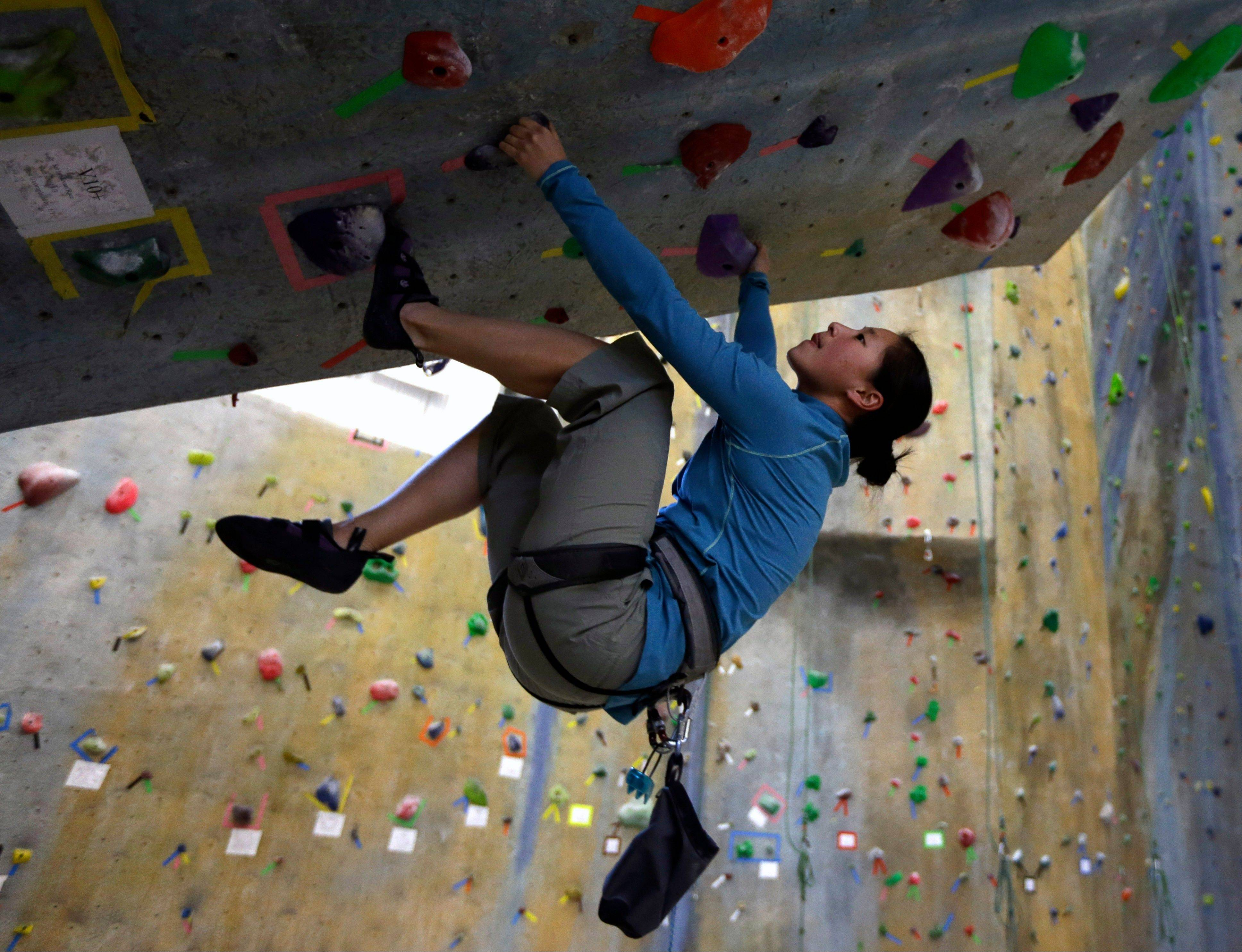 Helen Ho of Albany, N.Y., climbs a boulder at The Edge Halfmoon indoor climbing center in Halfmoon, N.Y. The design and the weeknight crowd at The Edge reflect two big trends in climbing: toward indoor gyms and low-elevation challenges that don't require a safety rope.