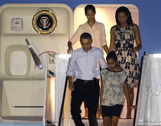 President Barack Obama arrives with first lady Michelle Obama, top, and daughters Malia, top left, and Sasha, bottom right, at Honolulu Joint Base Pearl Harbor-Hickam in Honolulu, for the start of their holiday vacation, Saturday, Dec. 22.