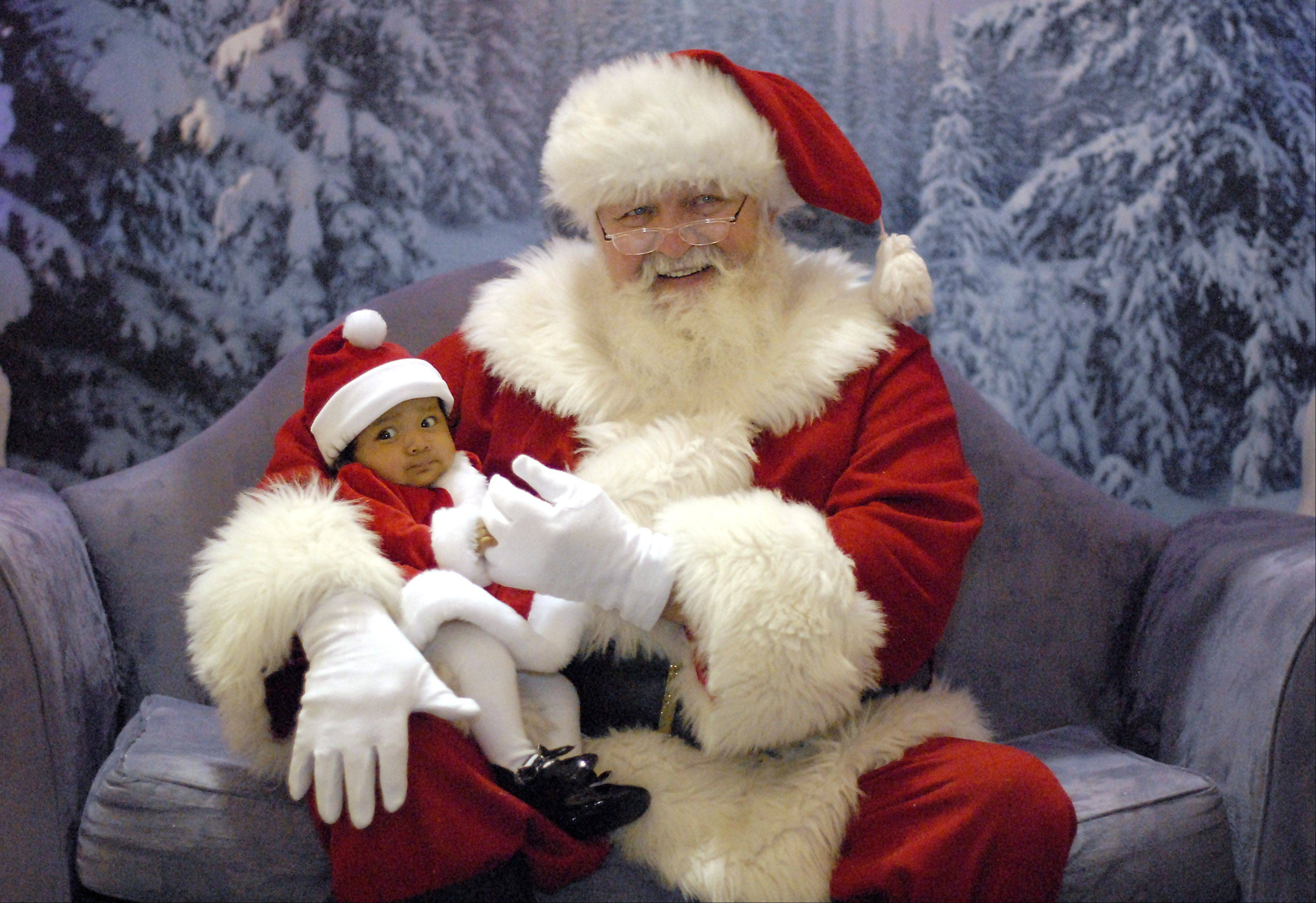 Santa Claus poses for a photo with 3-month-old Katie Bahena of Bartlett at Woodfield Mall in Schaumburg.