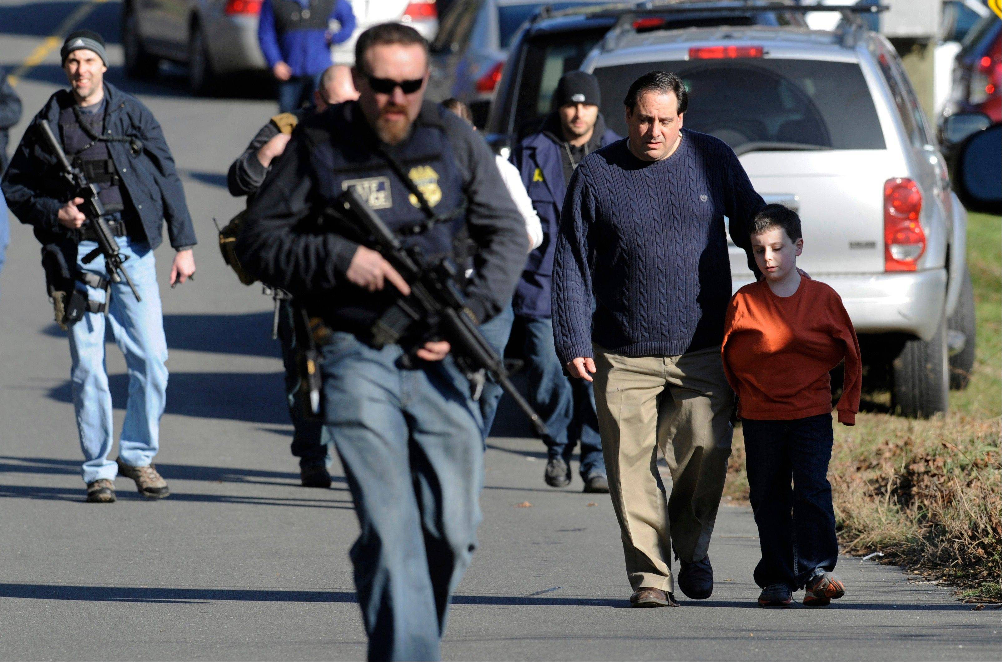 Parents leave a staging area after being reunited with their children following a shooting at the Sandy Hook Elementary School in Newtown, Conn., where a gunman fatally shot 27 people, including 20 children.