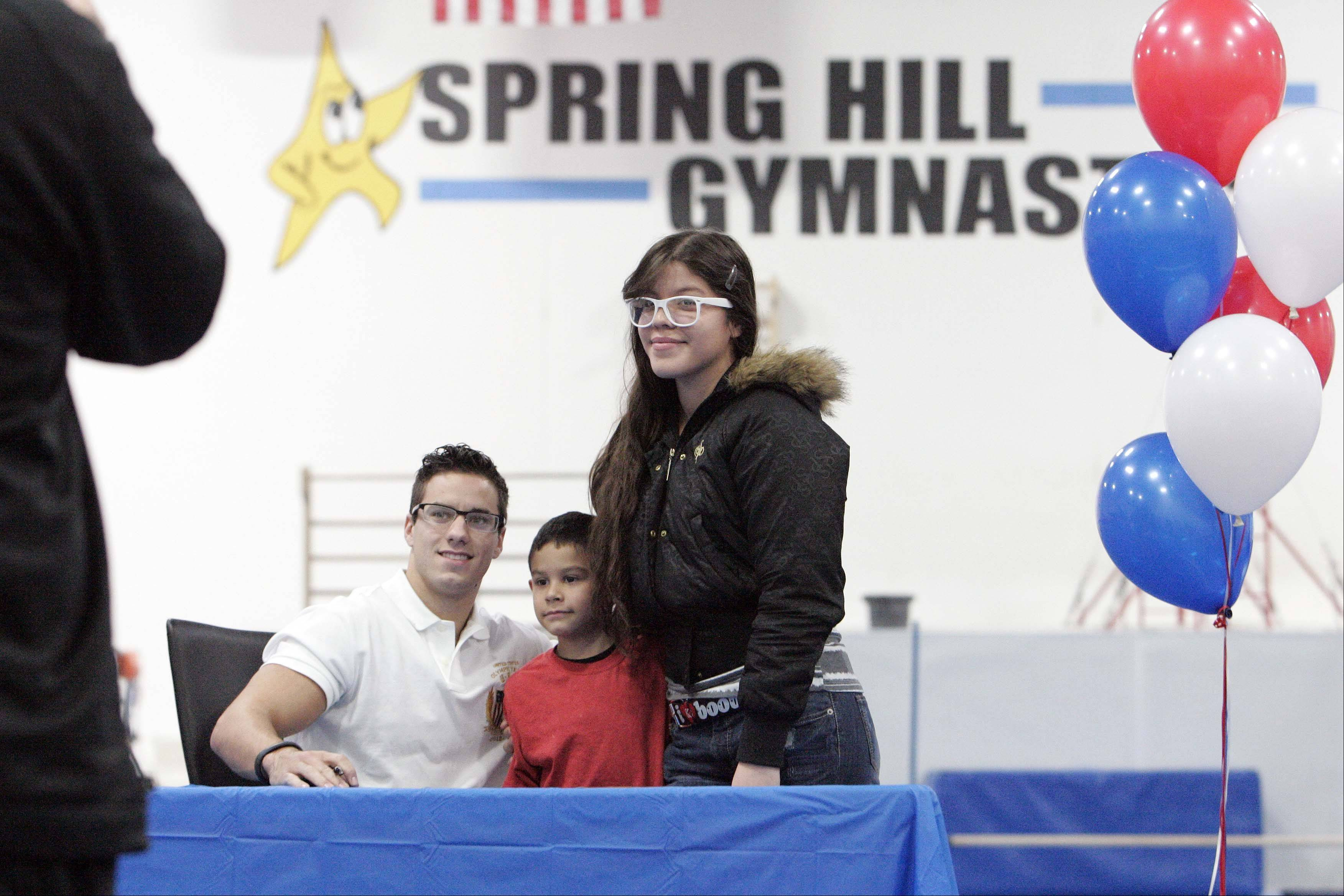 Six-year-old Juan Delgado and his sister Linda Marie Delgado, 18, both of Pingree Grove, get their picture taken with Olympic gymnast Jake Dalton on Saturday at Spring Hill Gymnastics in Elgin.