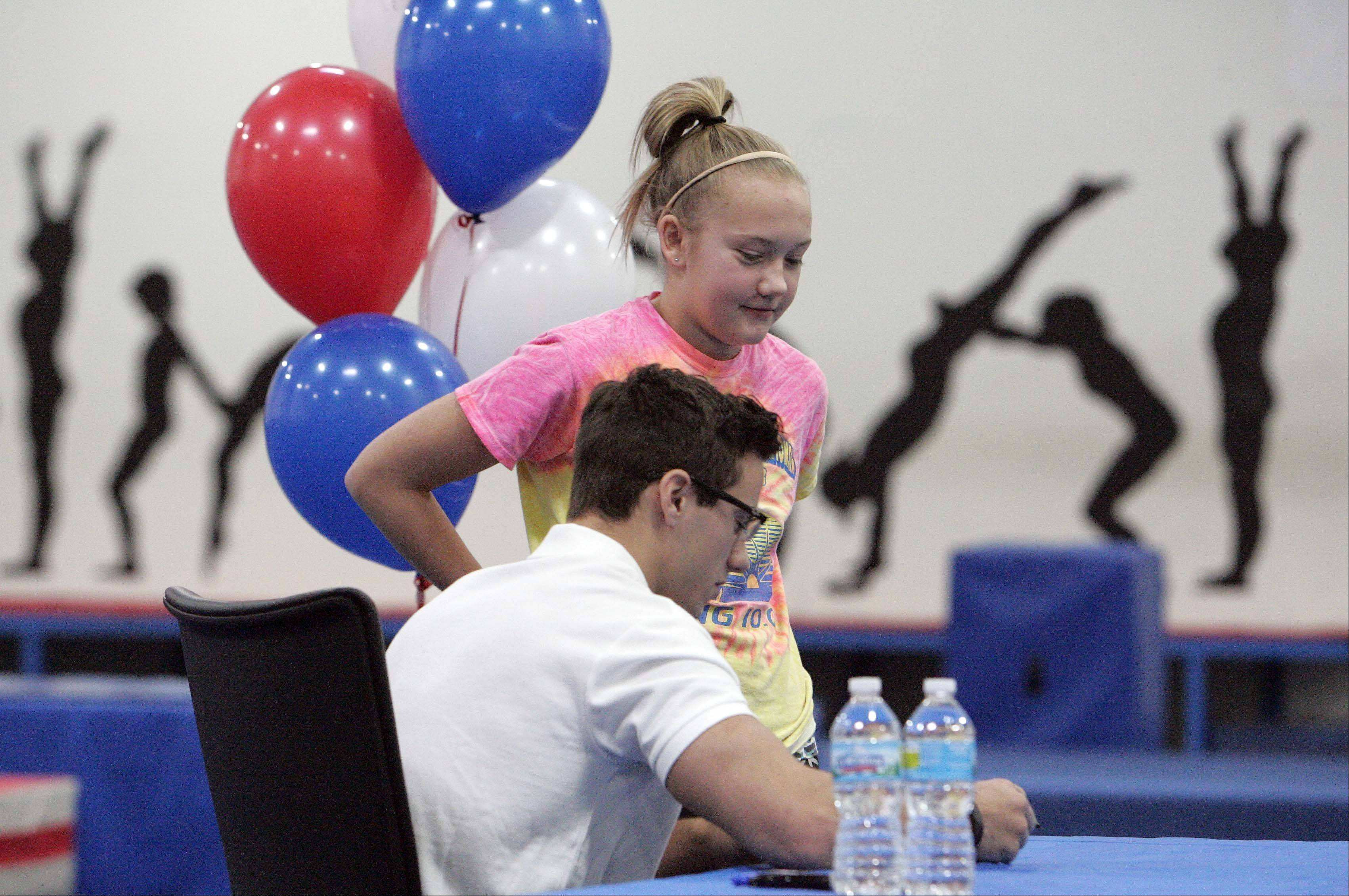 Olympic gymnast Jake Dalton signs an autograph on Saturday for 13-year-old Hailee Michel of Sleepy Hollow at Spring Hill Gymnastics in Elgin.