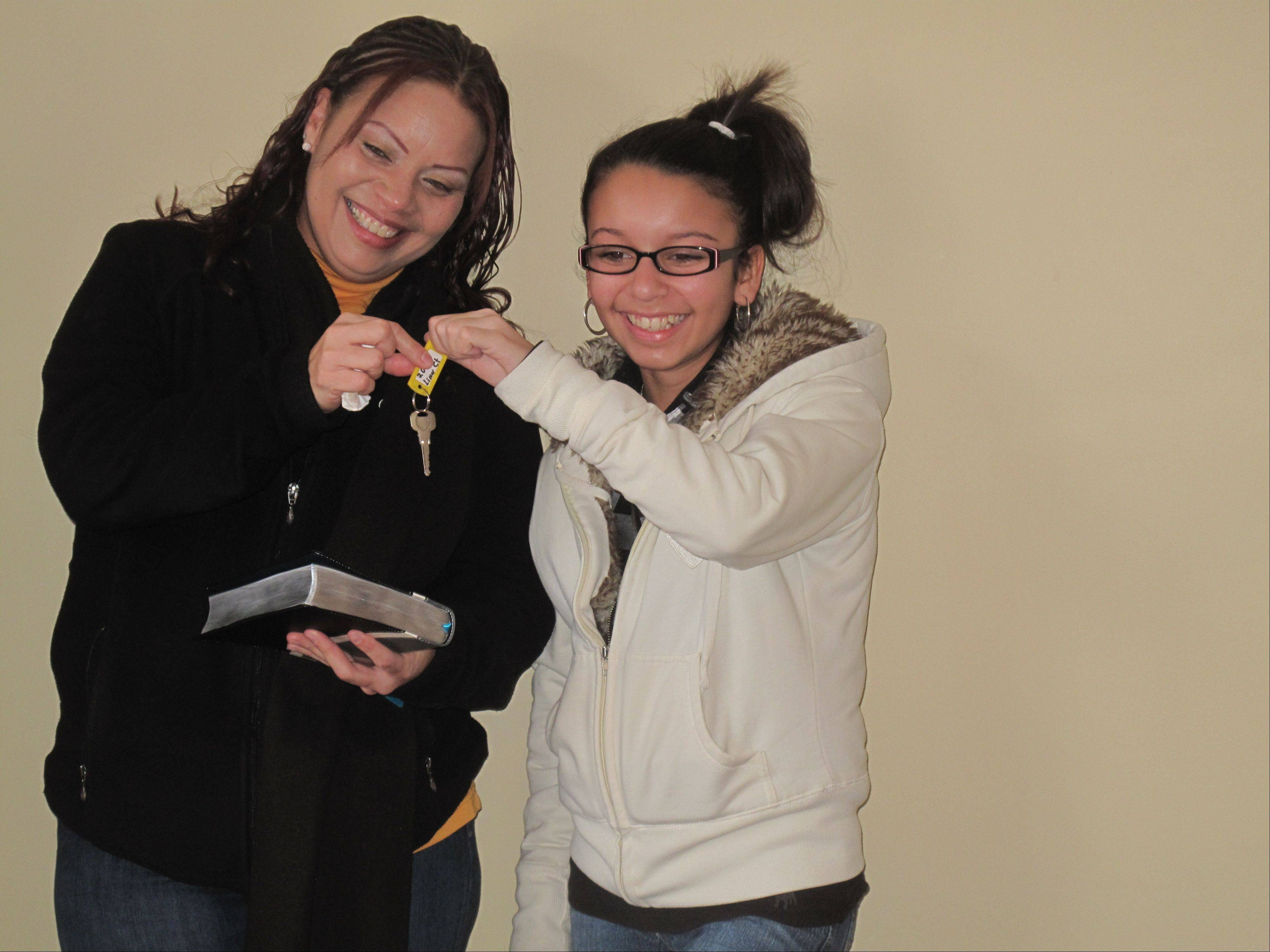 Enid Vargas and her daughter, 13-year-old Wilenid, hold keys to their new home on the 200 block of Linn Court in North Aurora during a ceremony Fox Valley Habitat for Humanity held Saturday to dedicate the home.