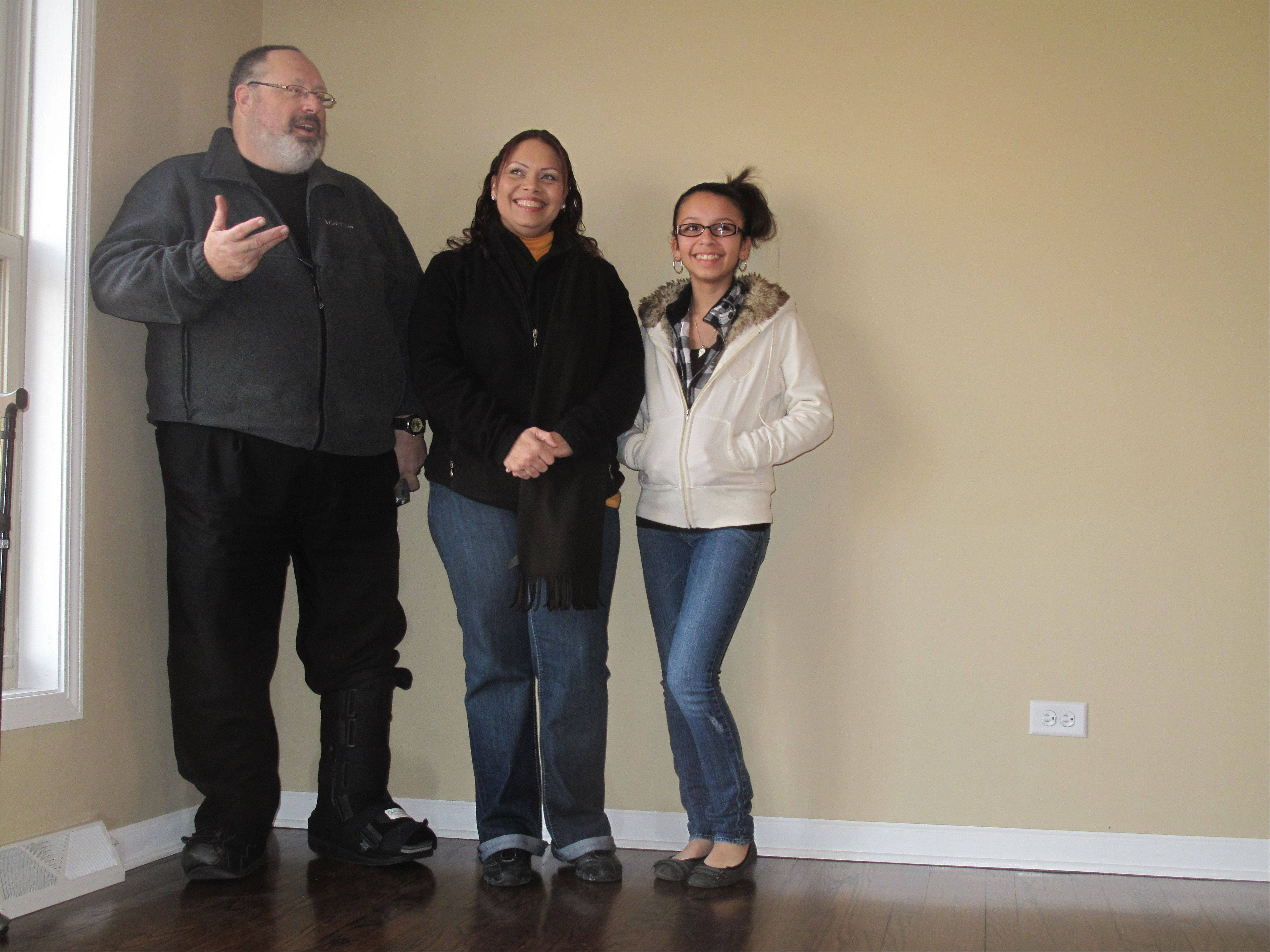 Jeff Barrett, executive director of Fox Valley Habitat for Humanity, introduces Enid Vargas and her daughter Wilenid, 13, Saturday during a ceremony dedicating a rehabbed North Aurora townhouse to the mother-daughter pair.
